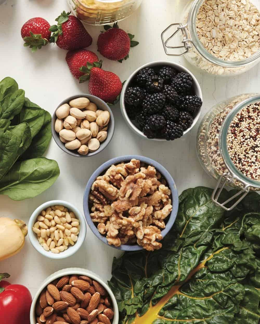 Overhead shot of bulk oats, quinoa, greens, nuts, and leafy greens.