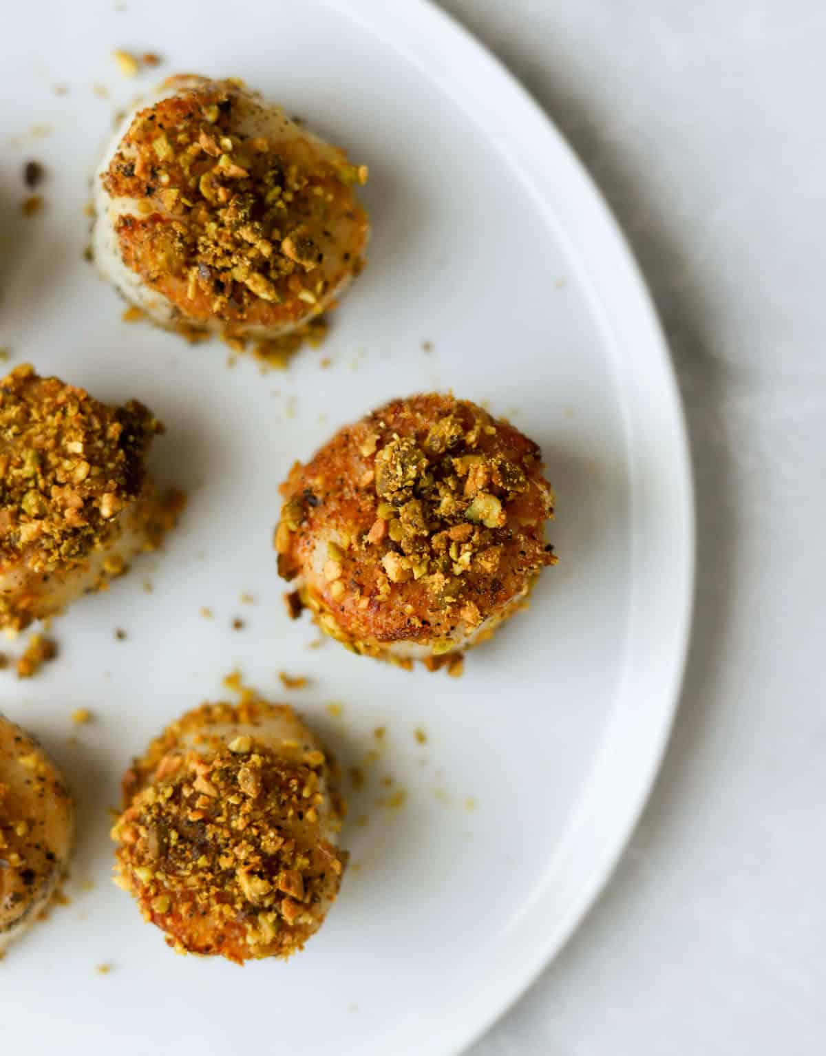 An overhead shot of a plate of pistachio crusted scallops.