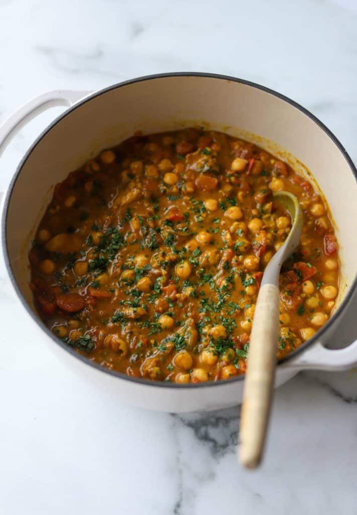 A white pot filled with chickpea coconut curry.