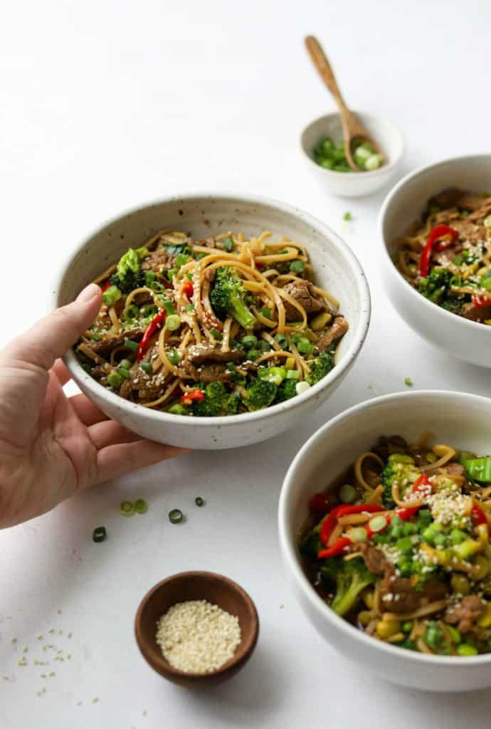 Side shot of Asian-Style Beef & Veggie Noodle Bowls with a hand holding one bowl.