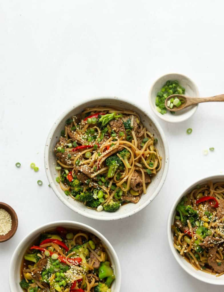 Overhead shot of Asian-Style Beef & Veggie Noodle Bowls in white bowls and chopped green onion on the side.