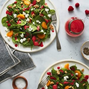 Spinach, Goat Cheese & Walnut Salad with Raspberry Vinaigrette on white plates