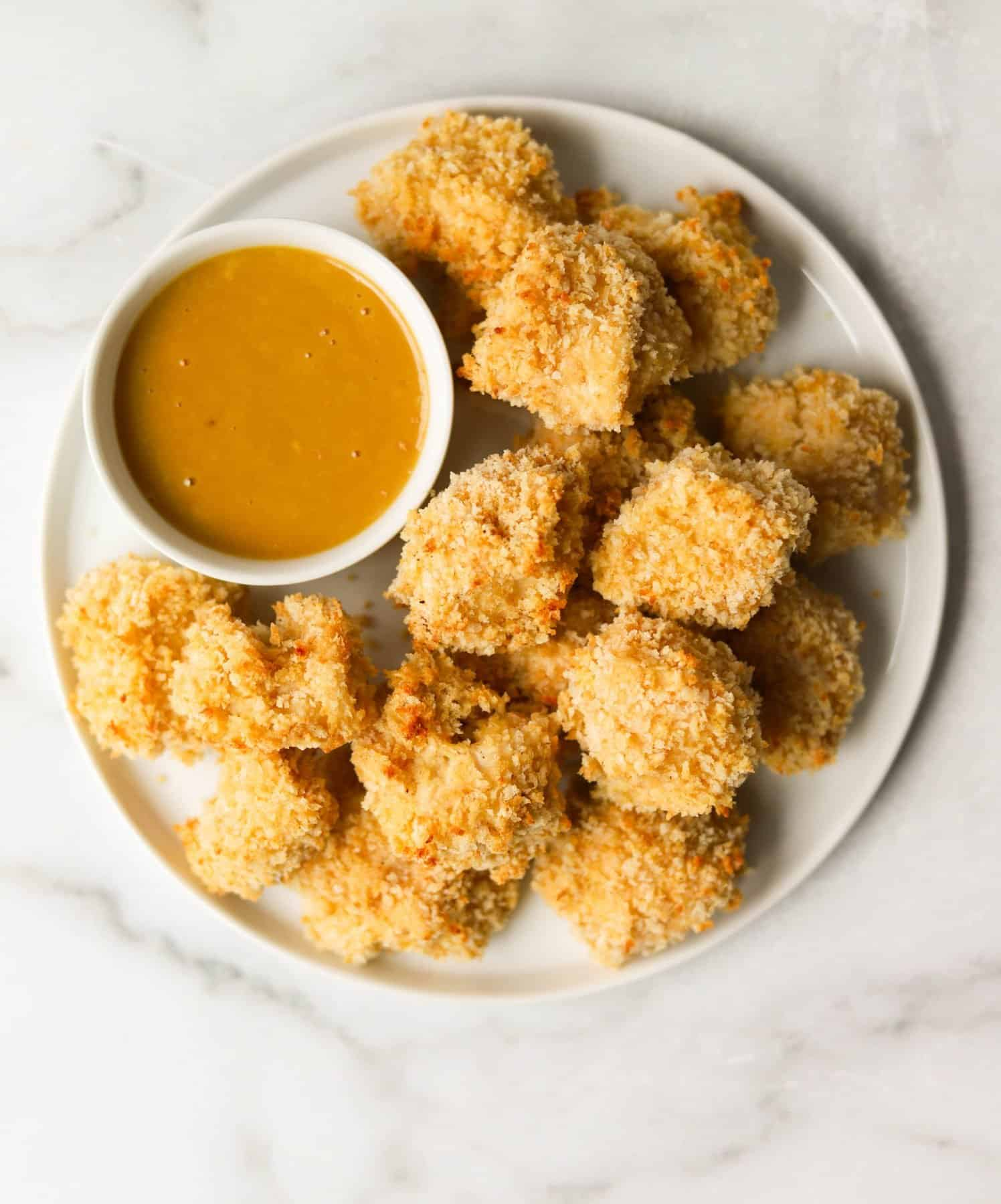 A white plate filled with healthy baked chicken nuggets with a bowl of honey mustard dipping sauce.