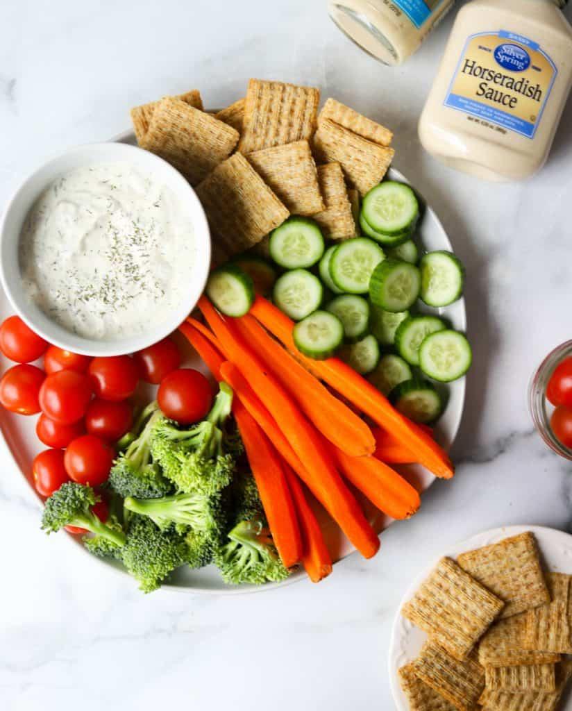 Plate full of veggies and crackers with horseradish dip
