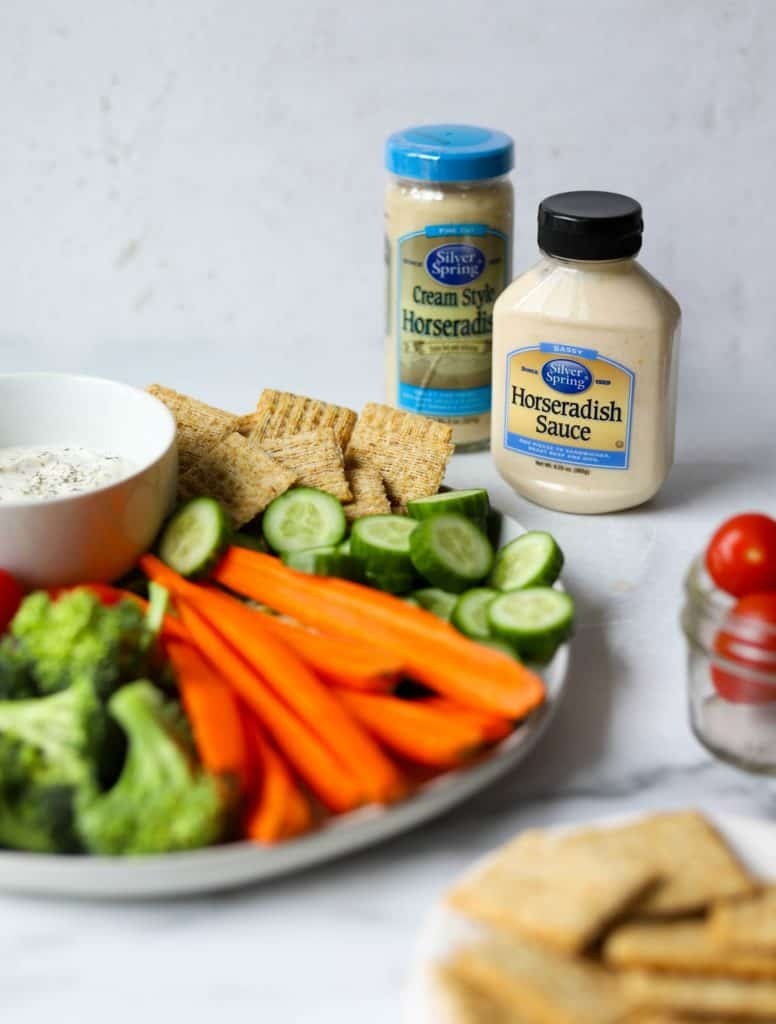 Veggie dip and condiments on white marble backdrop