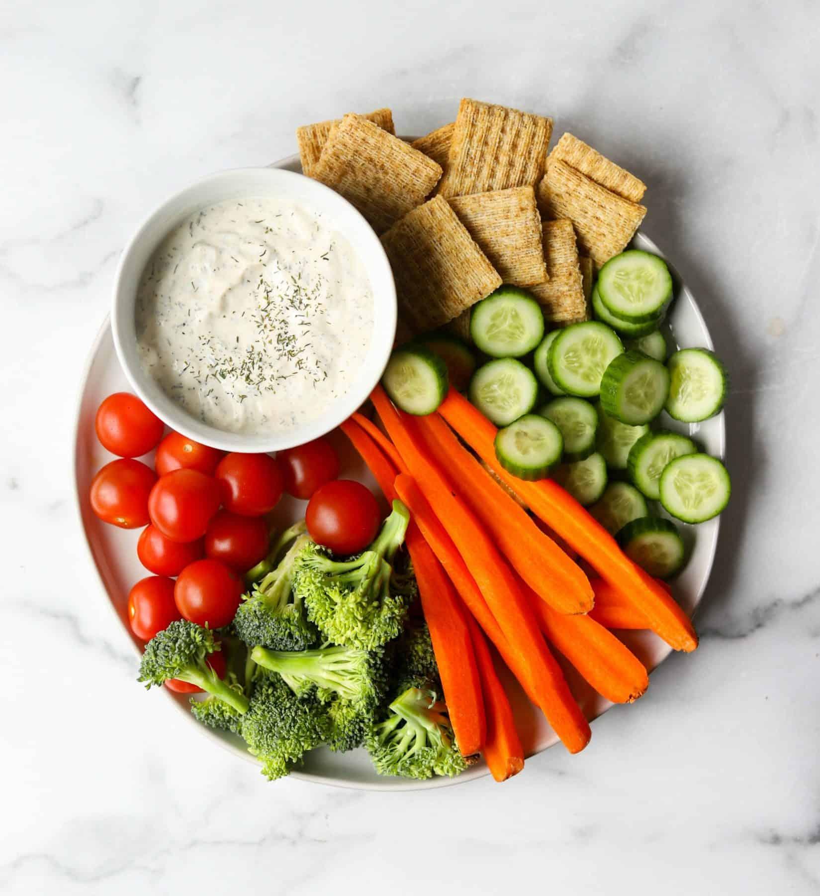 Veggie tray on white marble backdrop.
