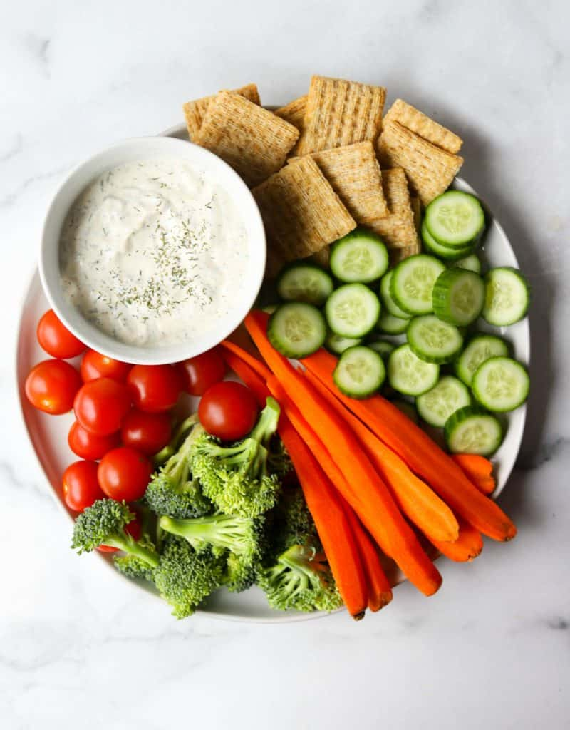 Veggie tray on white marble backdrop as an example of an easy way to eat more vegetables