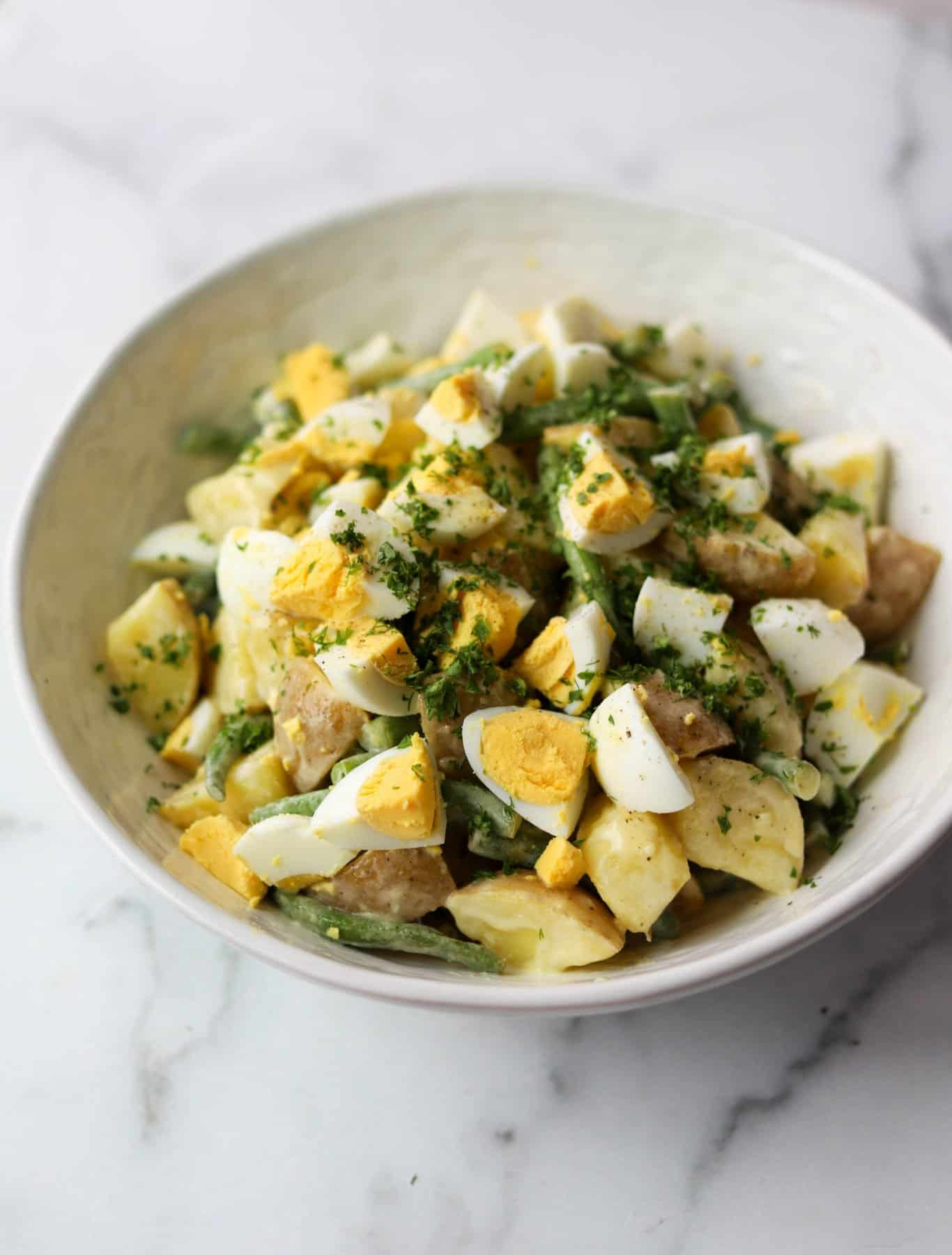 Green bean potato salad in a white bowl
