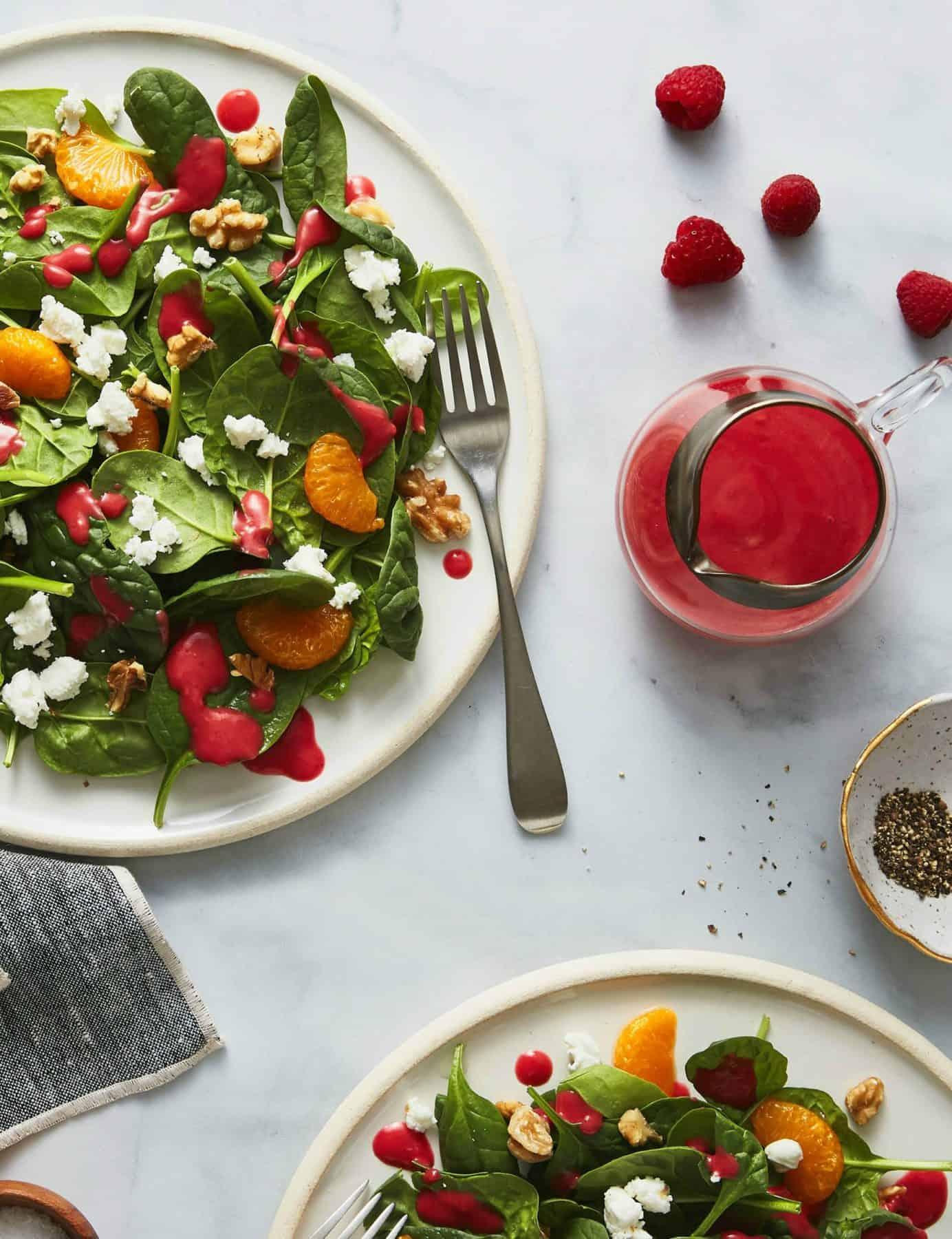 Salad on white plates with raspberry dressing in a carafe