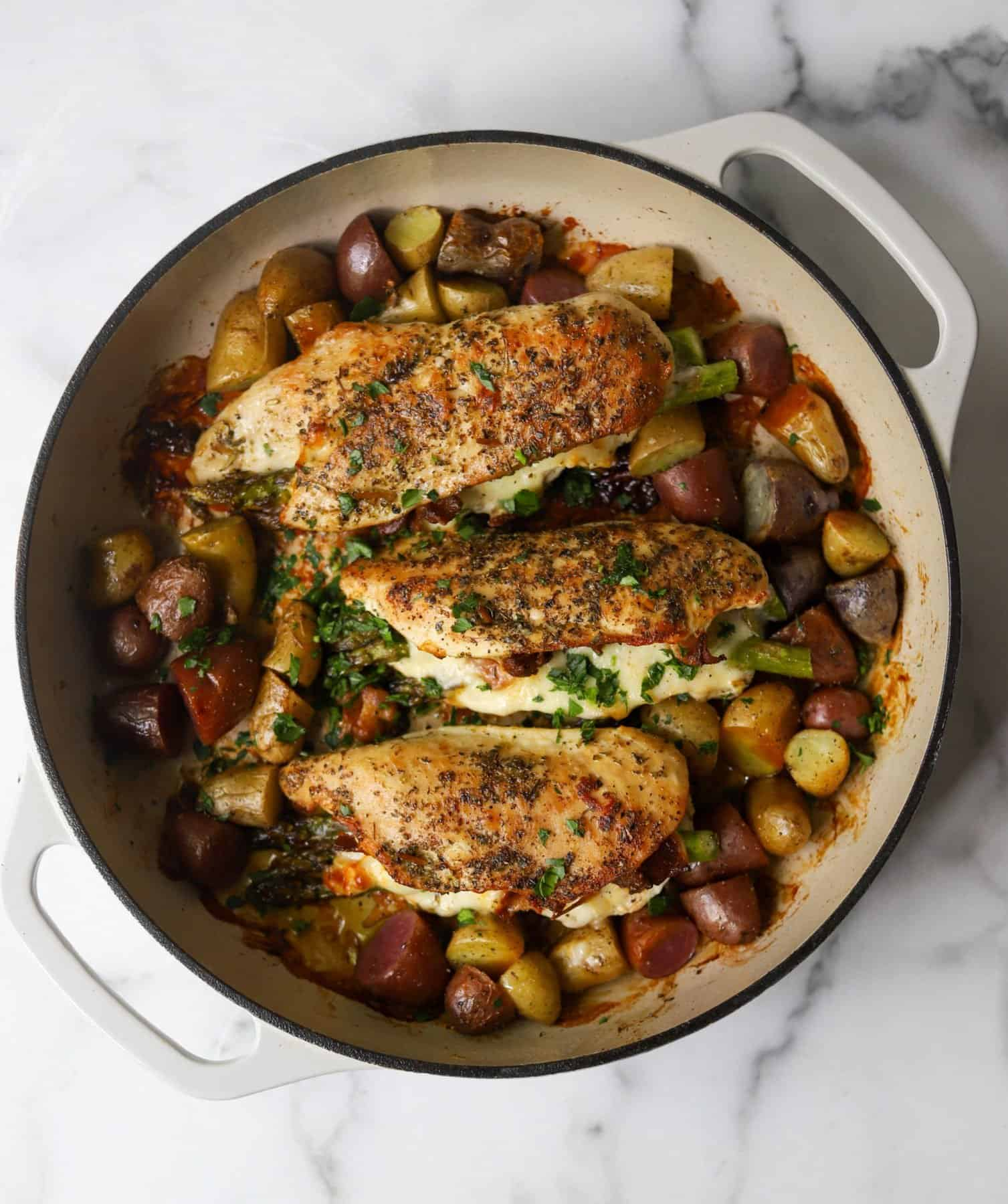 Asparagus stuffed chicken and potatoes in a white dish as a healthy one pot meal