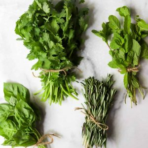 Bunches of herbs on a white marble backdrop
