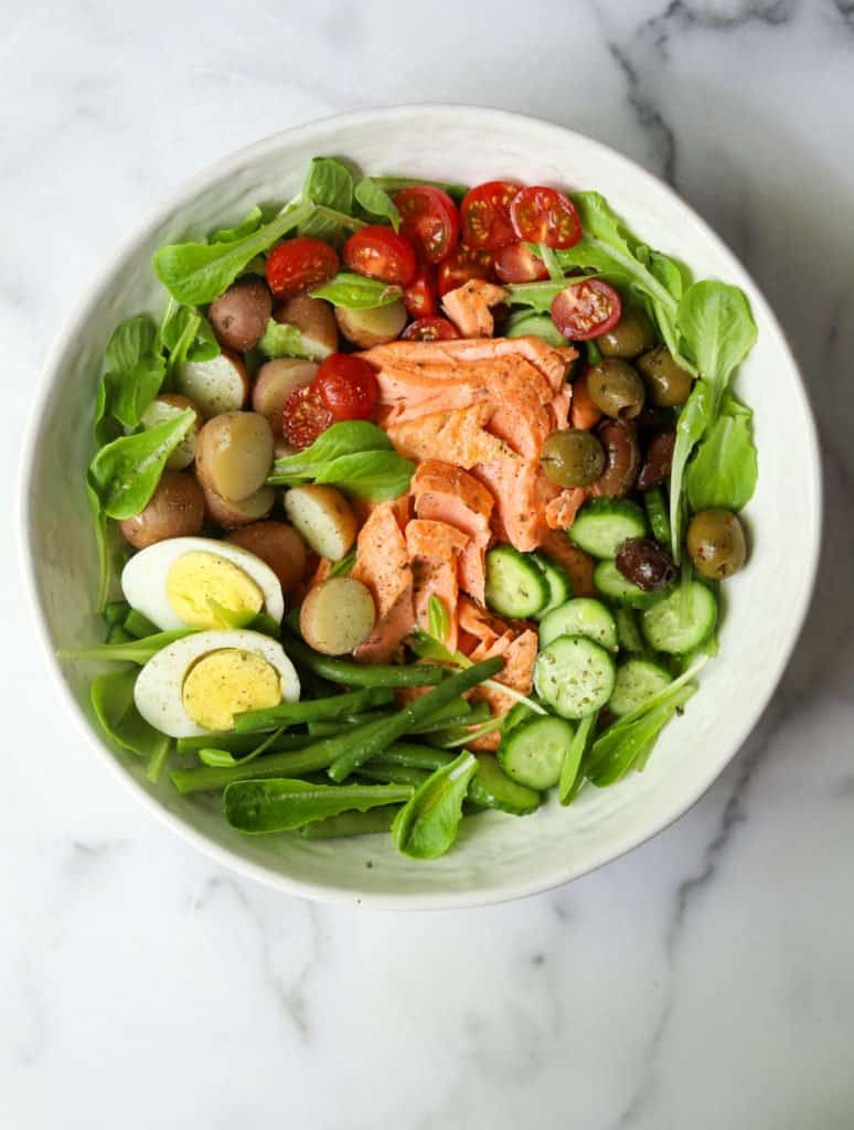 Salmon Nicoise Salad in a white bowl with eggs, potatoes and vegetables as a balanced salad example