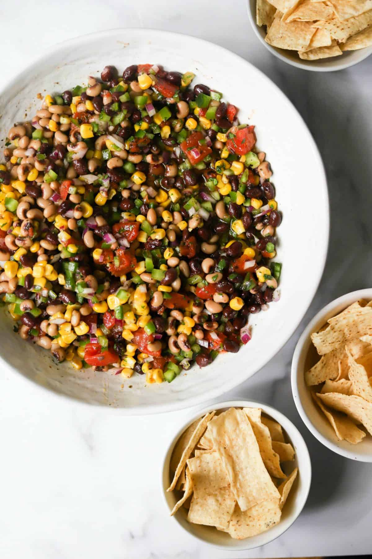 Cowboy caviar in a white bowl with tortilla chips made with canned black beans.