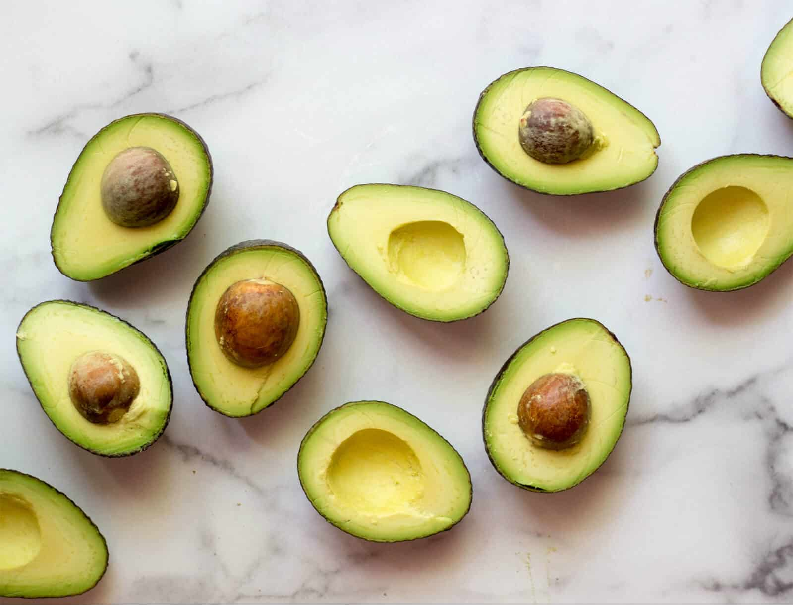 Halved avocados on a white marble board.