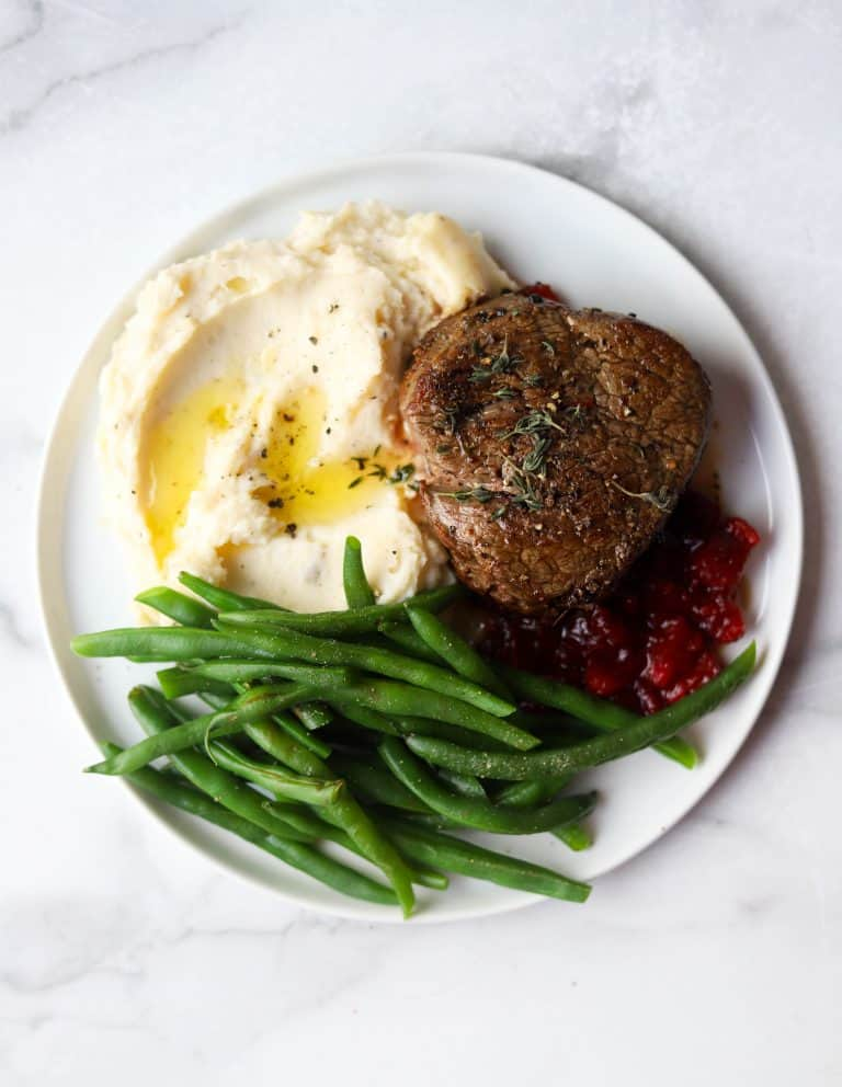 Beef tenderloin, green beans, mashed potatoes and cranberry compote on a white plate