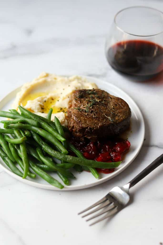 Beef tenderloin, green beans, mashed potatoes and cranberry compote on a white plate with wine and fork in the background