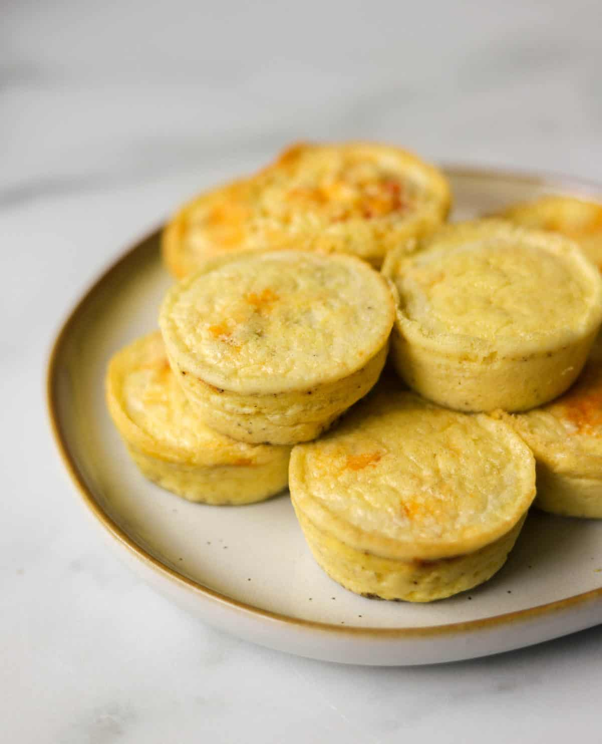 A side shot of a plate of stacked egg bites.