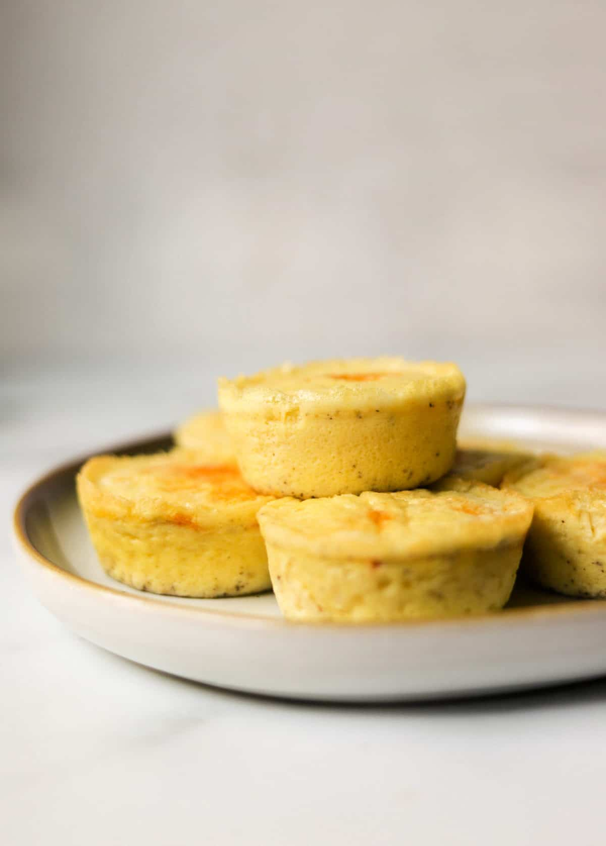 A side shot of a plate stacked with egg bites.