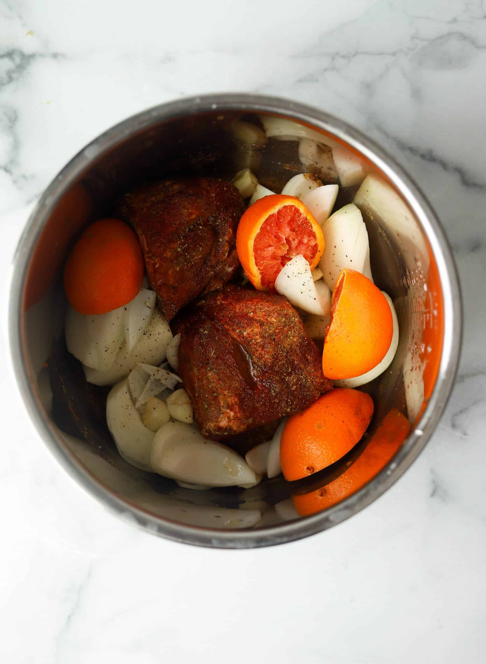 An pot filled with pork shoulder, onions, garlic and oranges.