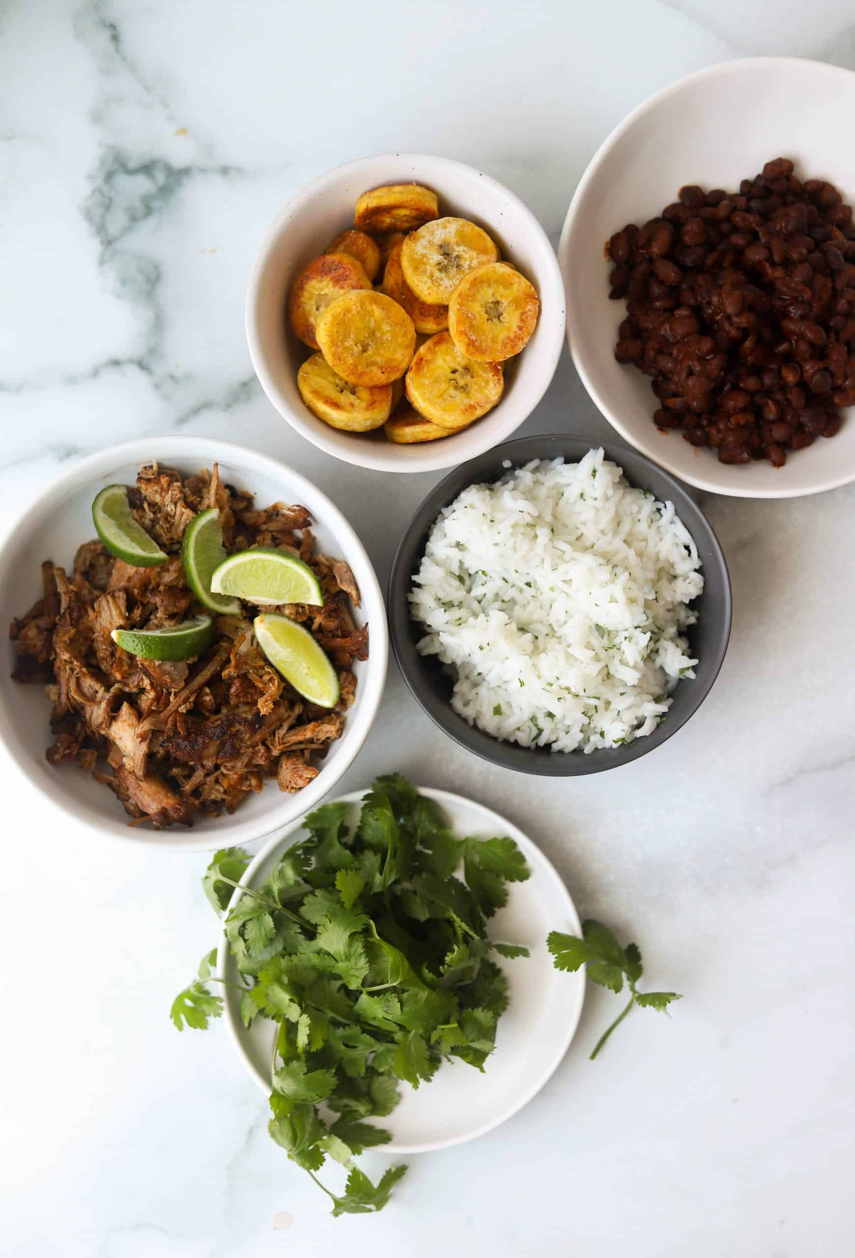Small white bowls filled with cuban pork, rice, black beans, fried plantains and cialntro.