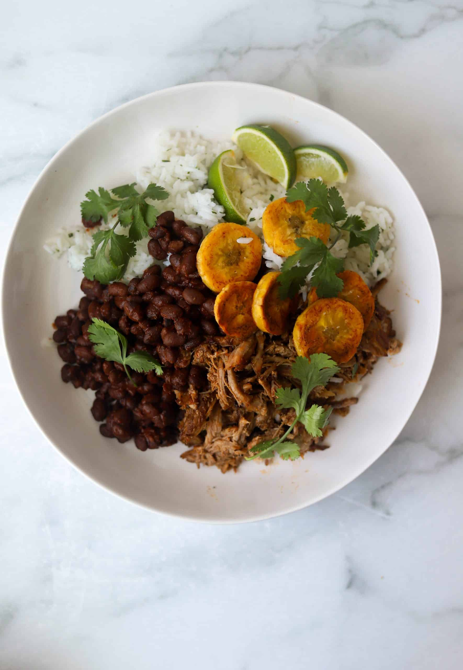 A large white bowl filled with cuban pork, rice, black beans and fried plantains.
