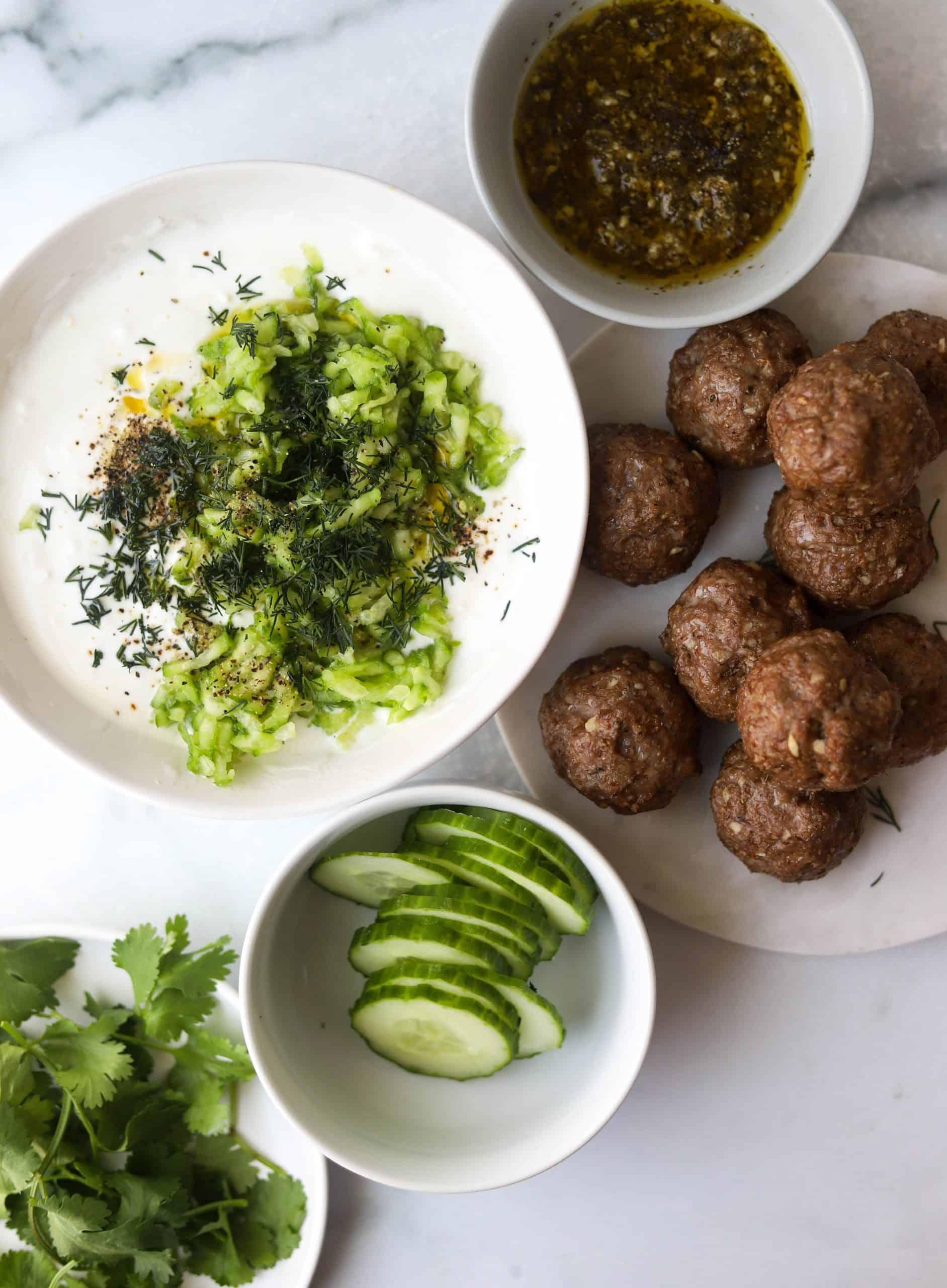 Ingredients for greek lamb meatball gyros in separate bowls.
