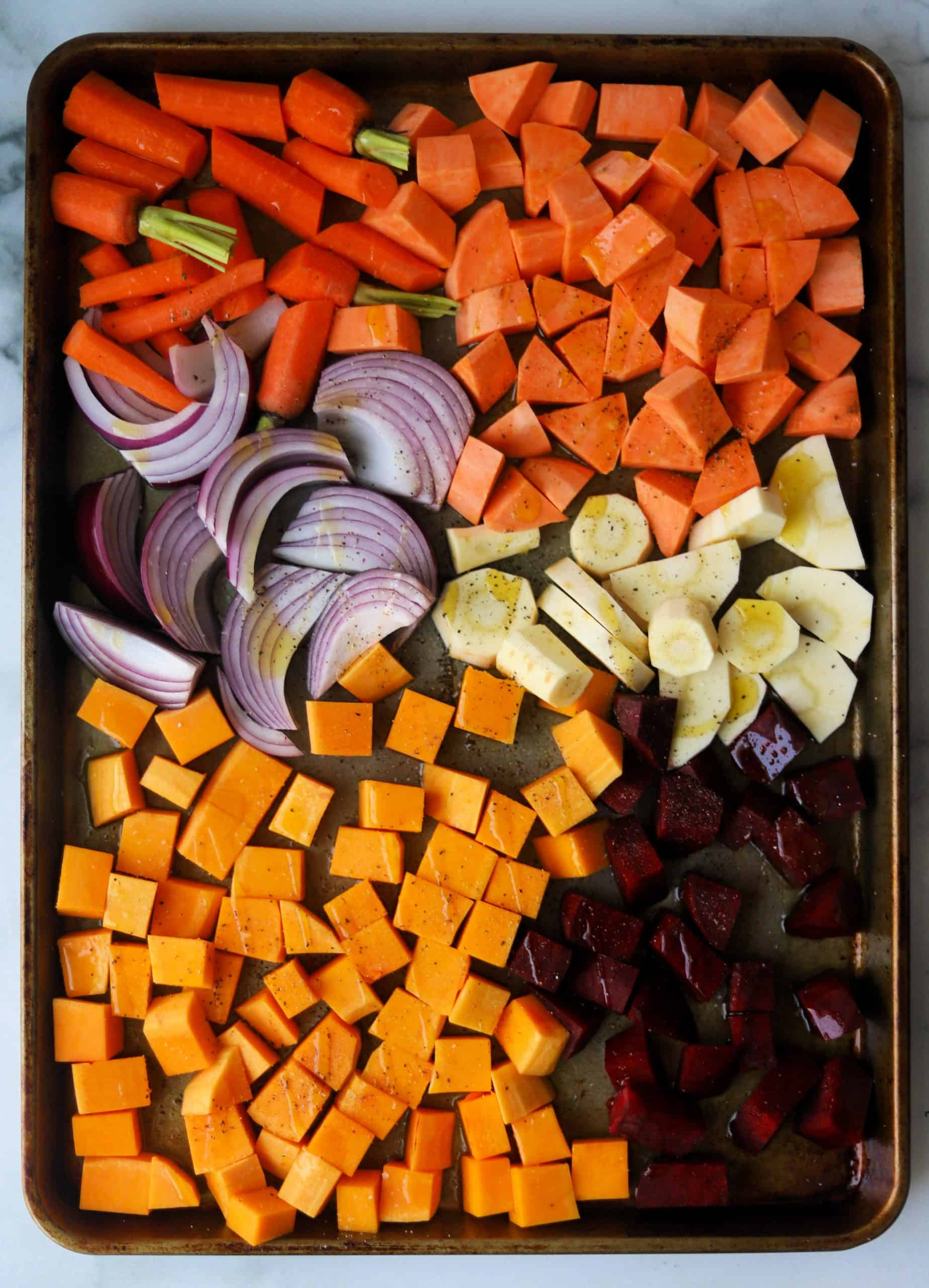 Chopped vegetables drizzled with olive oil and seasoned with salt and pepper on a sheet pan.