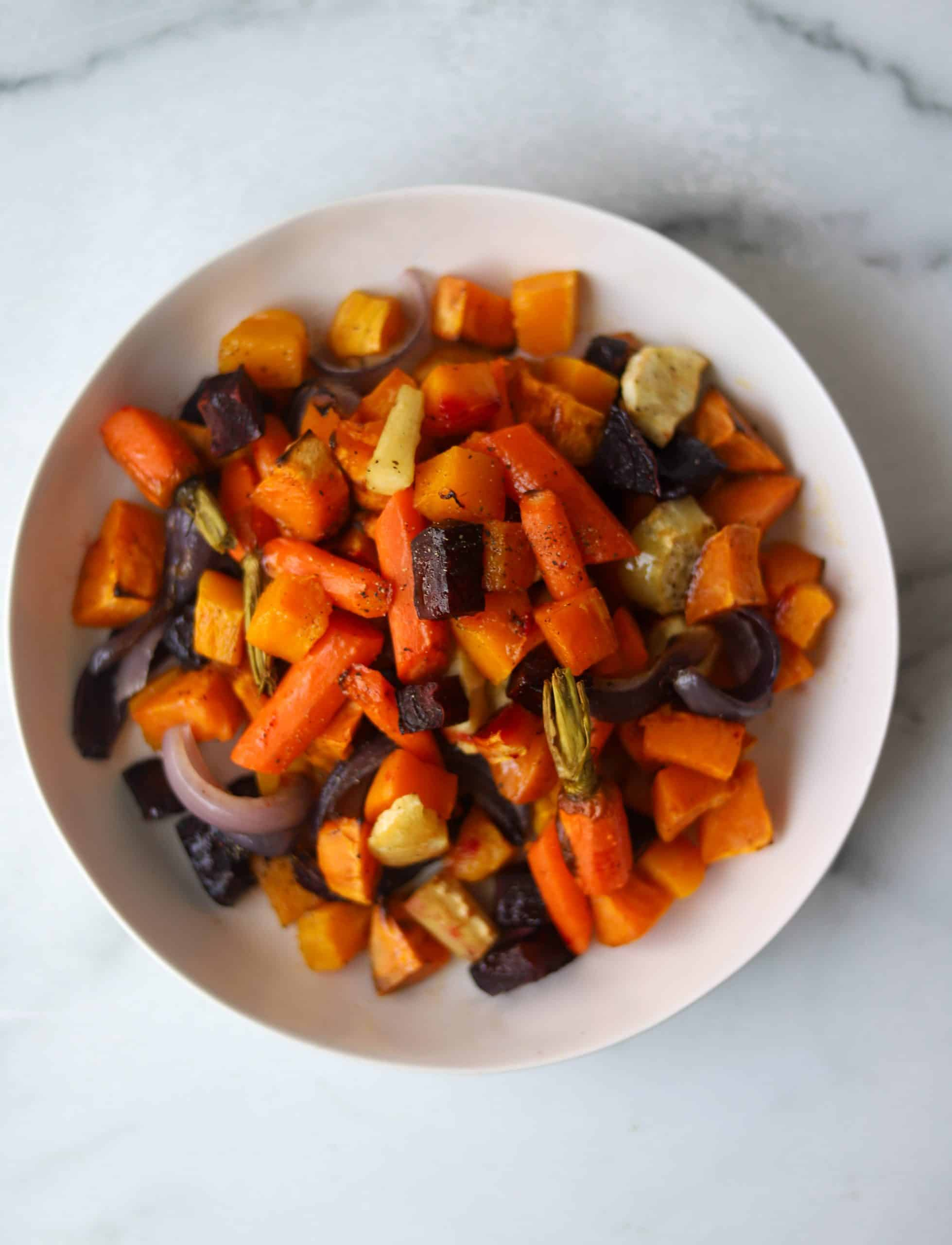 Roasted vegetables piled on each other in a white bowl.