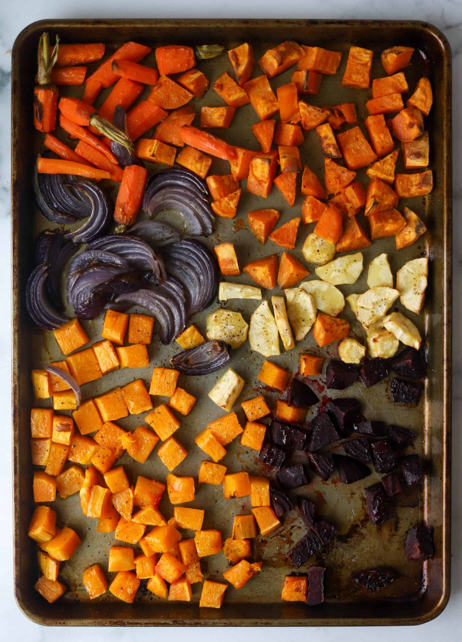 Chopped and roasted carrots, sweet potatoes, onions, parsnips, and beets  fresh out of the oven on a sheet pan.