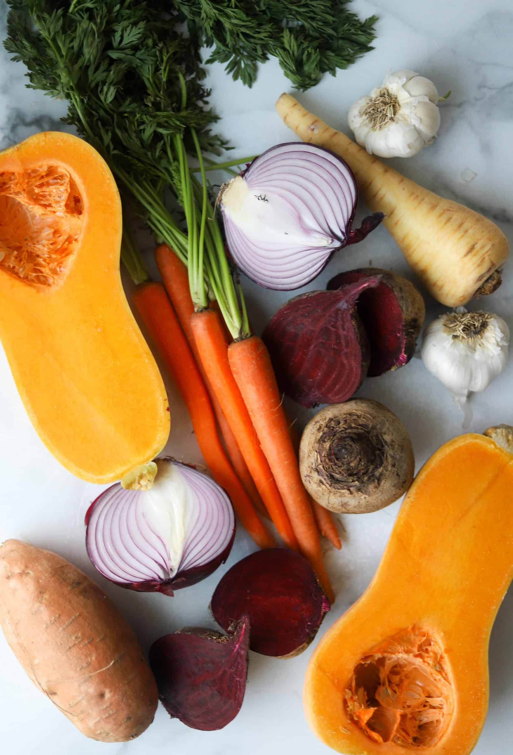 Multiple different vegetables on a marble backdrop.
