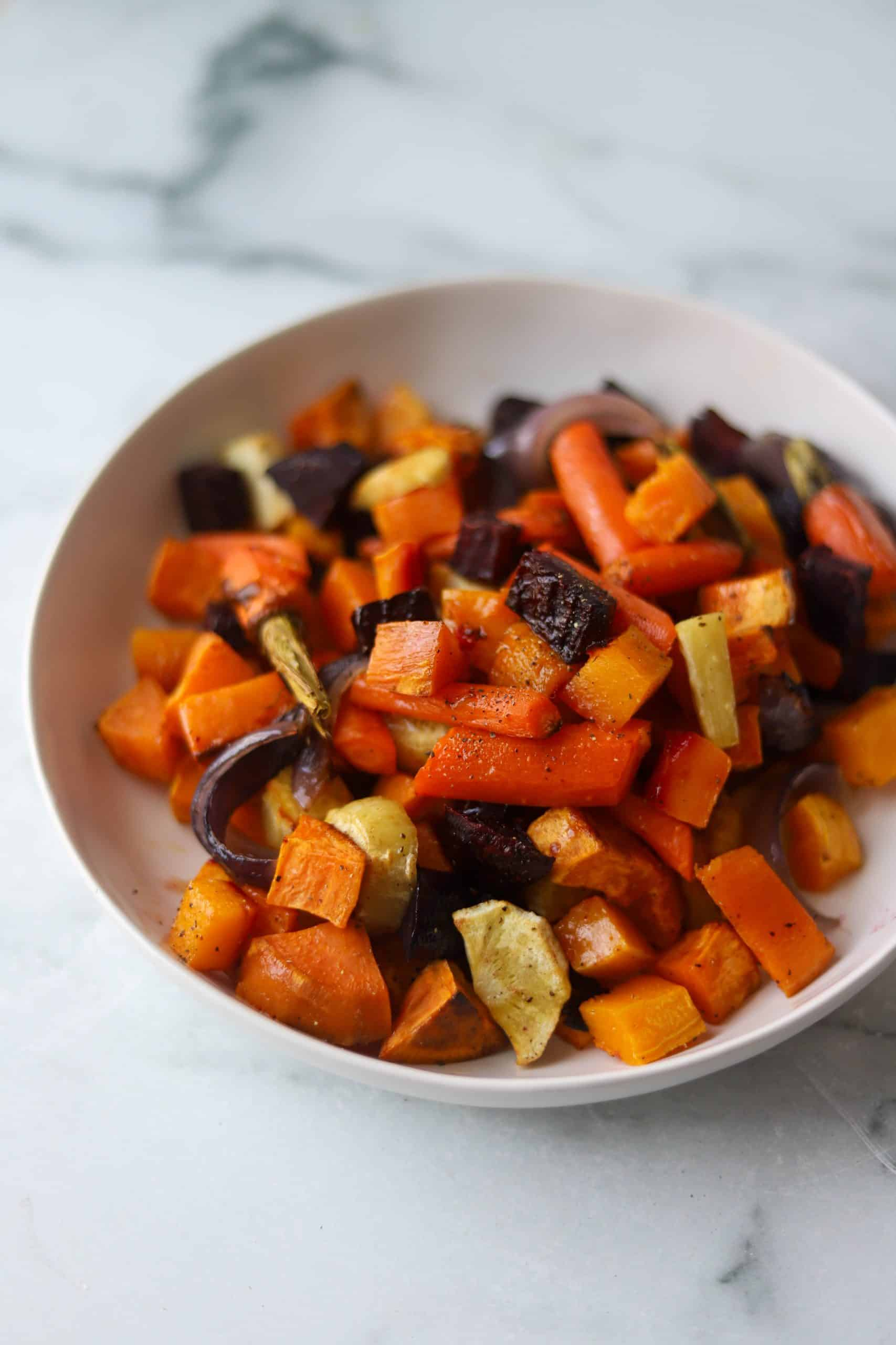 Side angle shot of roasted vegetables piled on each other in a white bowl.