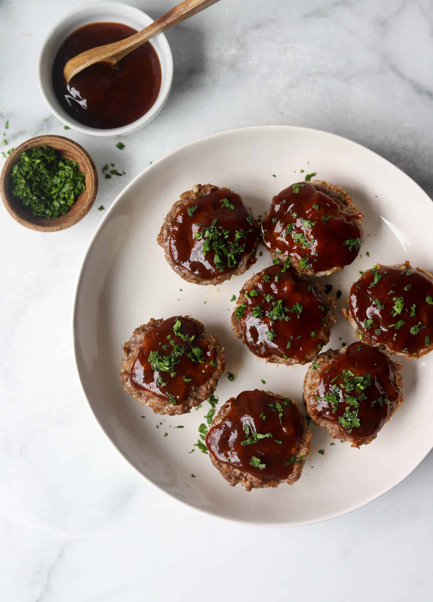 A plate of meatloaf cups with a small bowl of glaze and herbs.