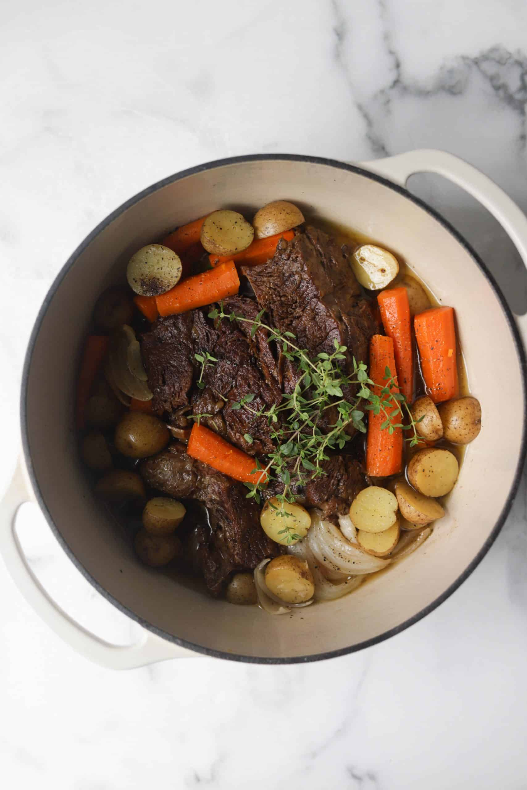 A white pot filled with beef pot roast.