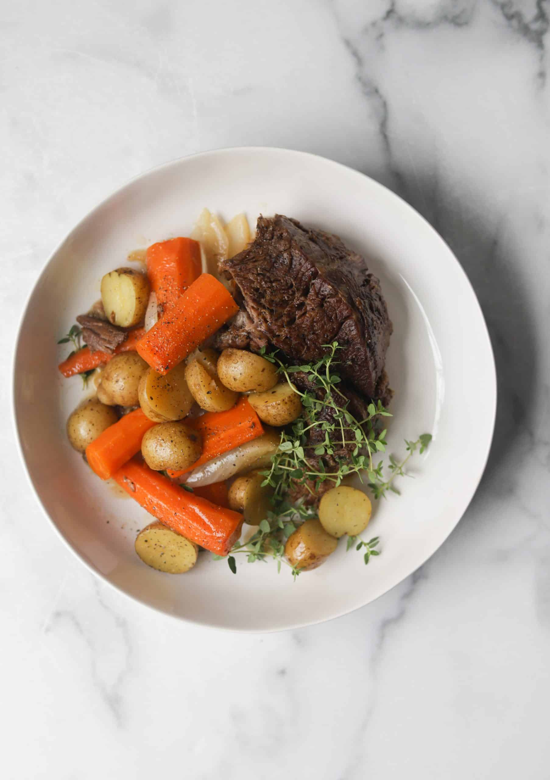 A white bowl filled with beef pot roast