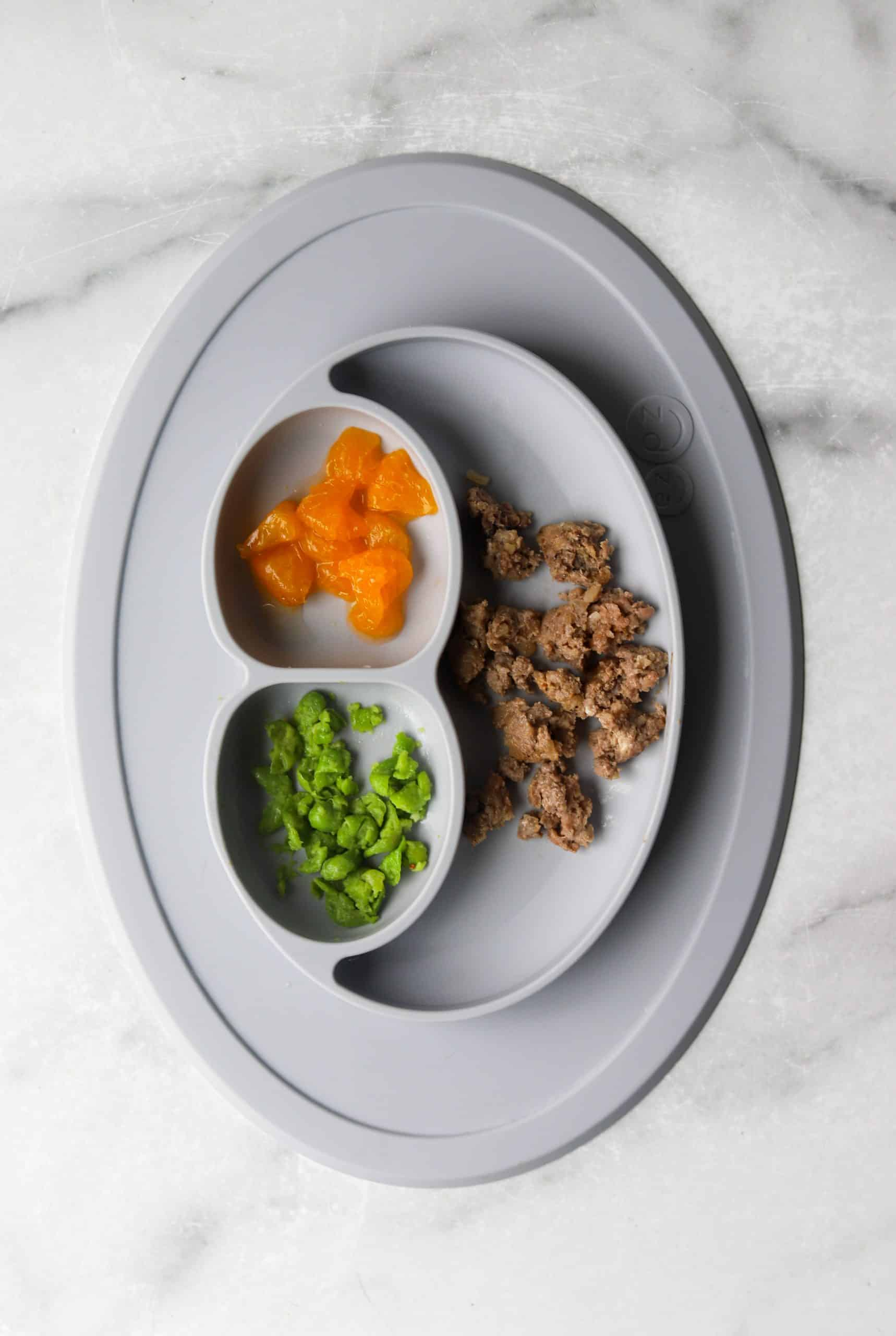 A plate of meatloaf, peas and mandarin oranges prepared for a toddler.