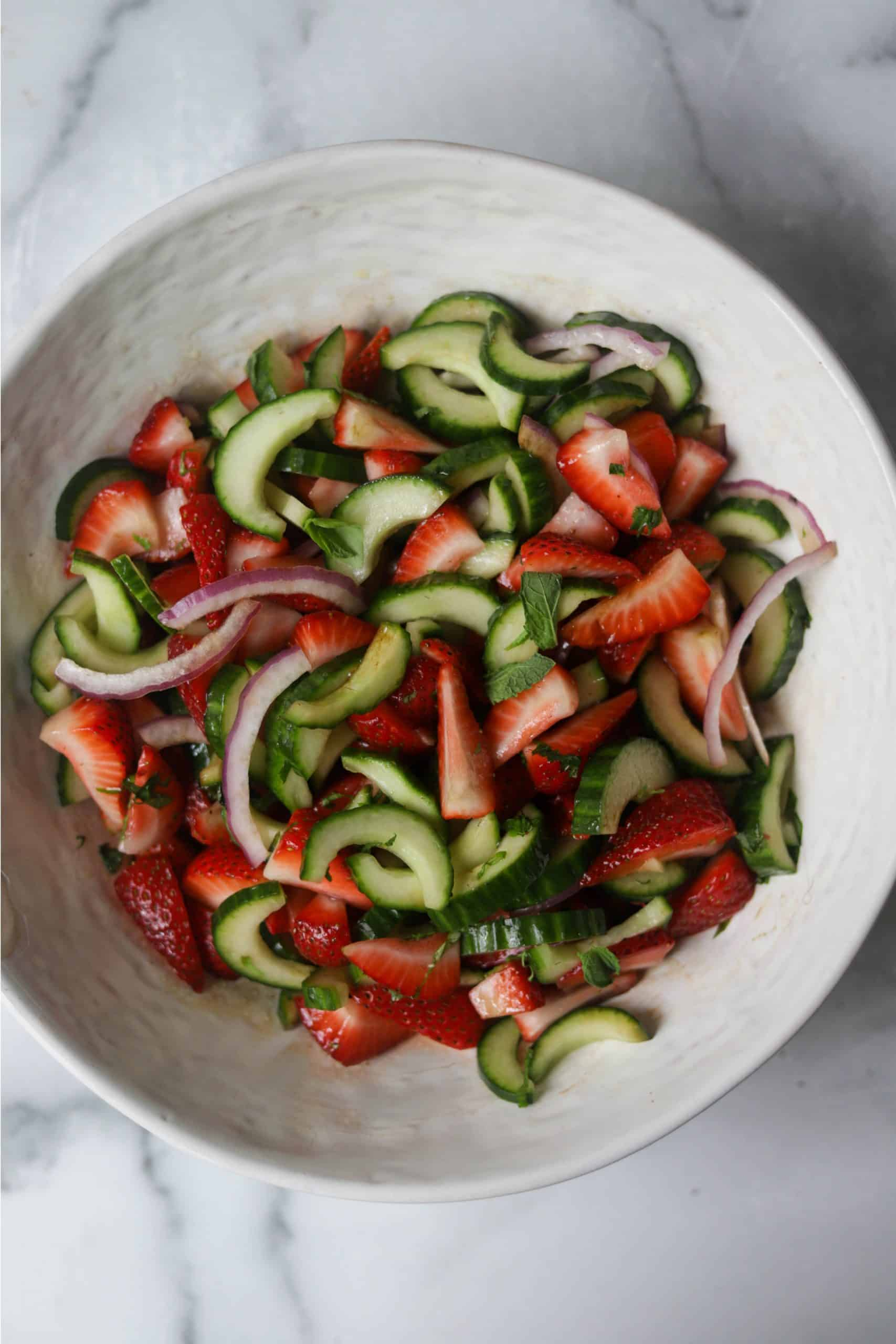 A white bowl filled with strawberry cucumber salad.