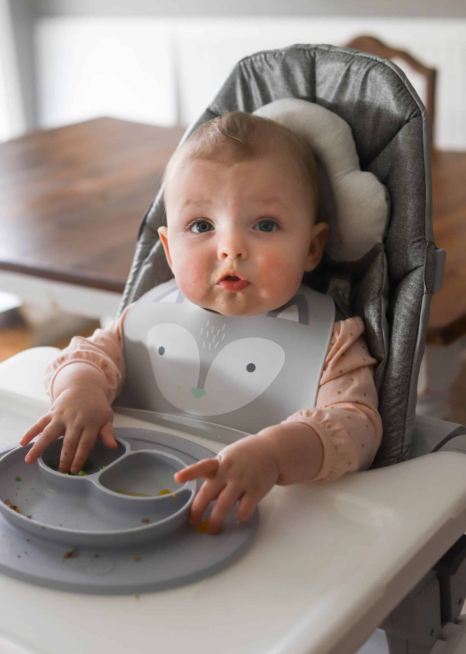A child in a bib at a high chair eating solid foods.