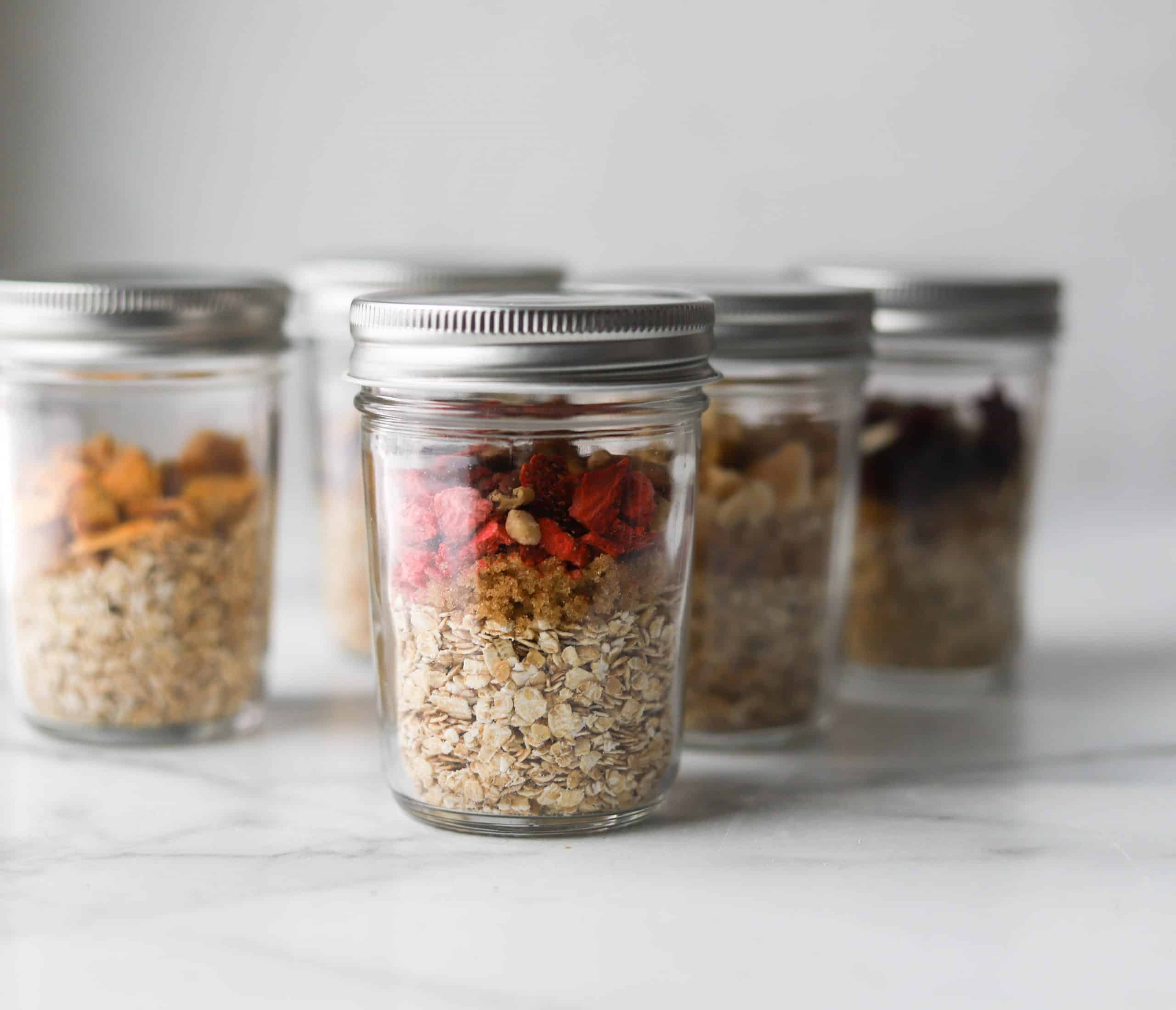 Instant oatmeal ingredients in small clear jars on a marble surface.