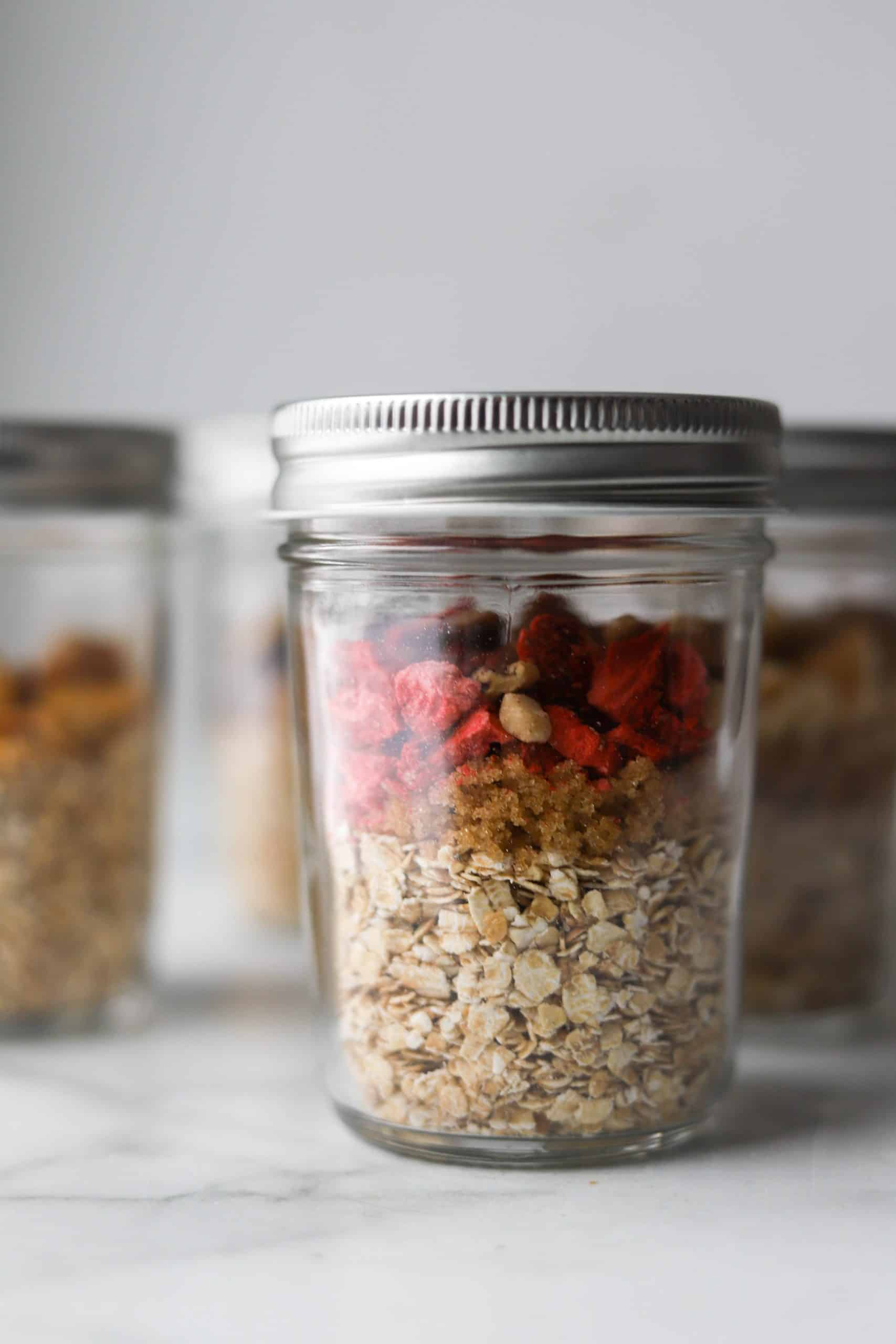 Clear jars filled with oatmeal ingredients on a white marble backdrop.