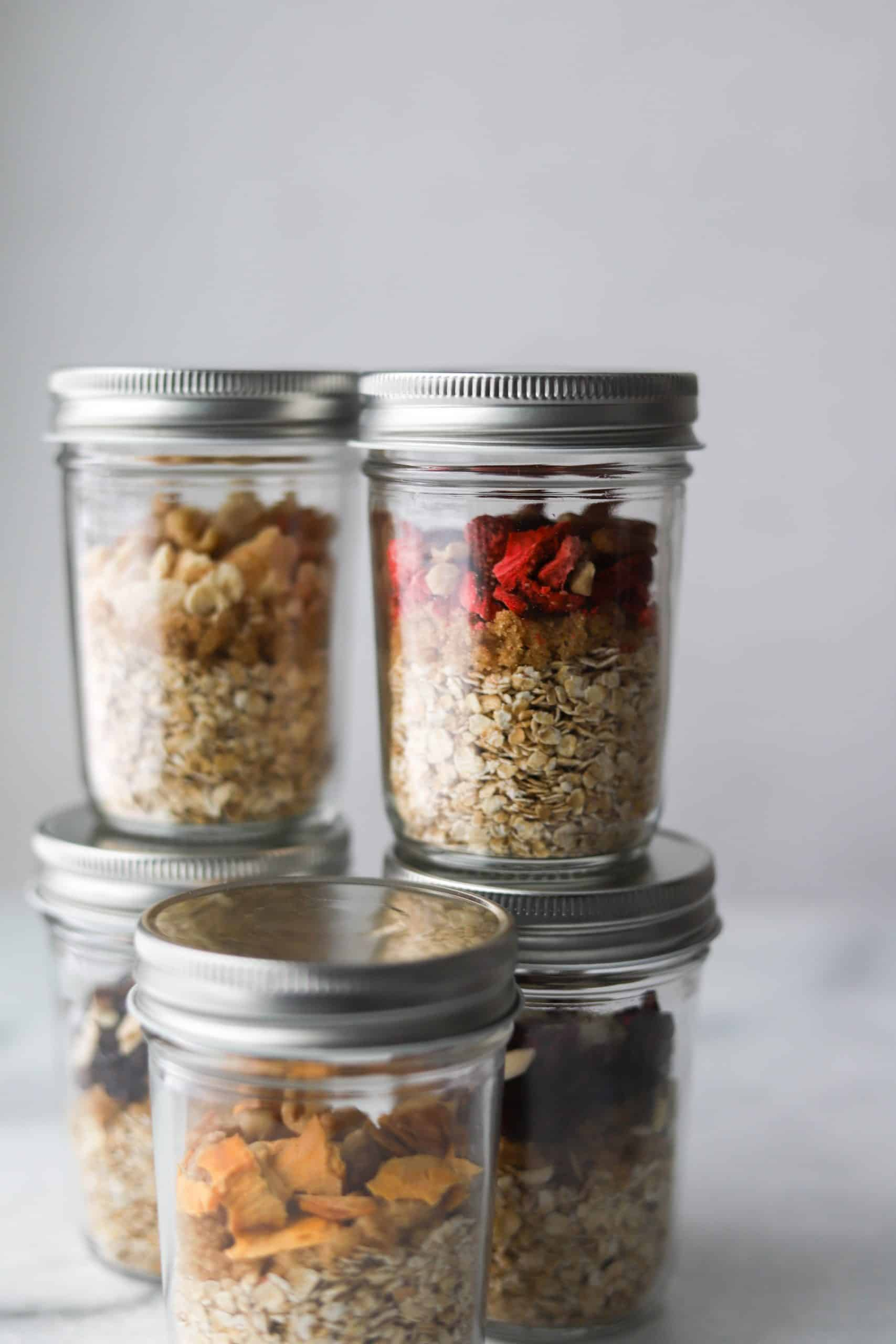 Jars filled with oatmeal cup ingredients on a white marble backdrop.
