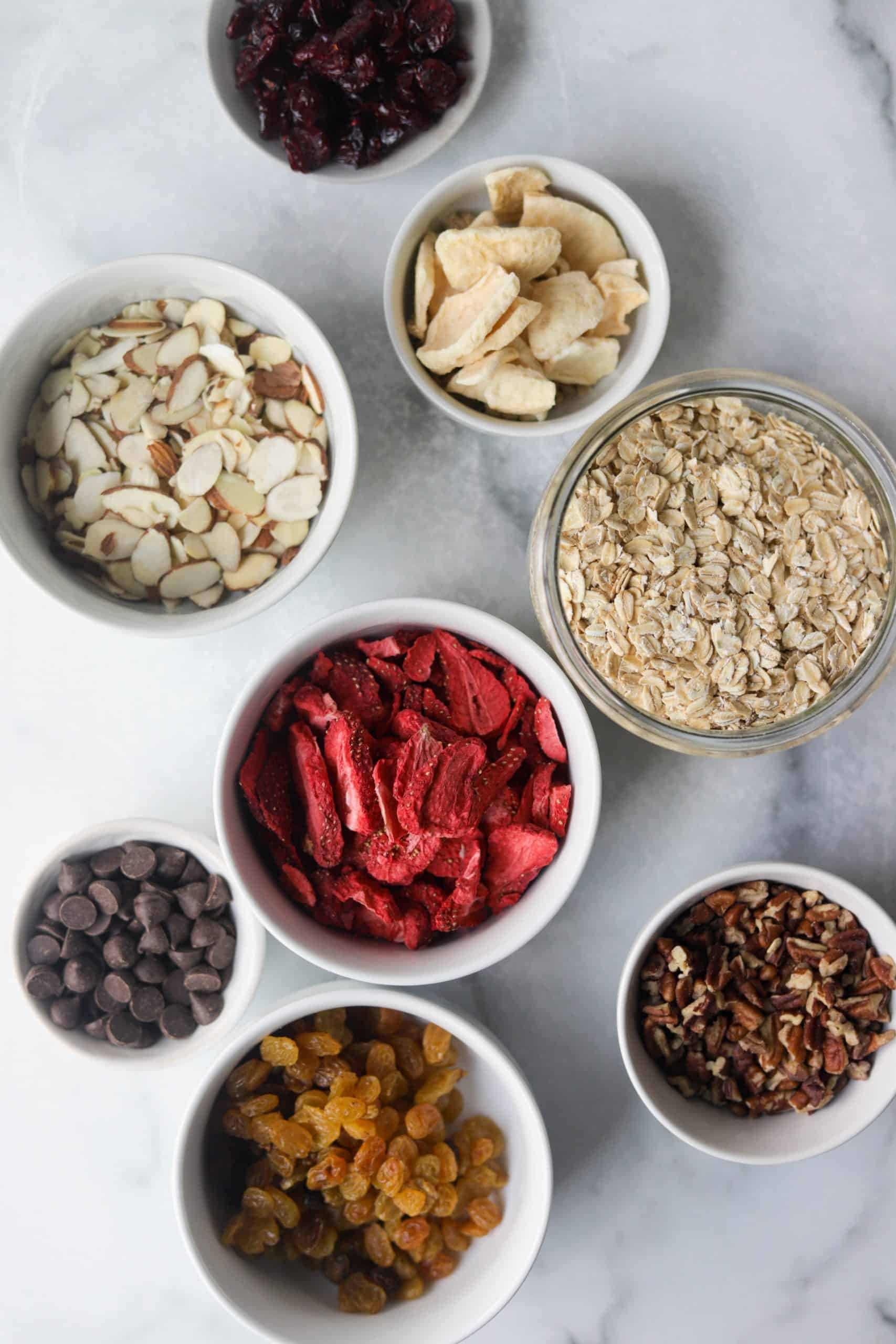Bowls of oatmeal ingredients like dried fruit and nuts on a marble backdrop.