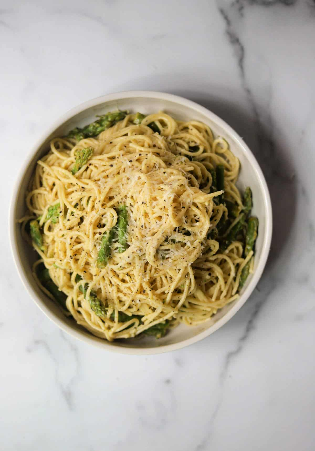 A white bowl filled with lemon asparagus pasta.