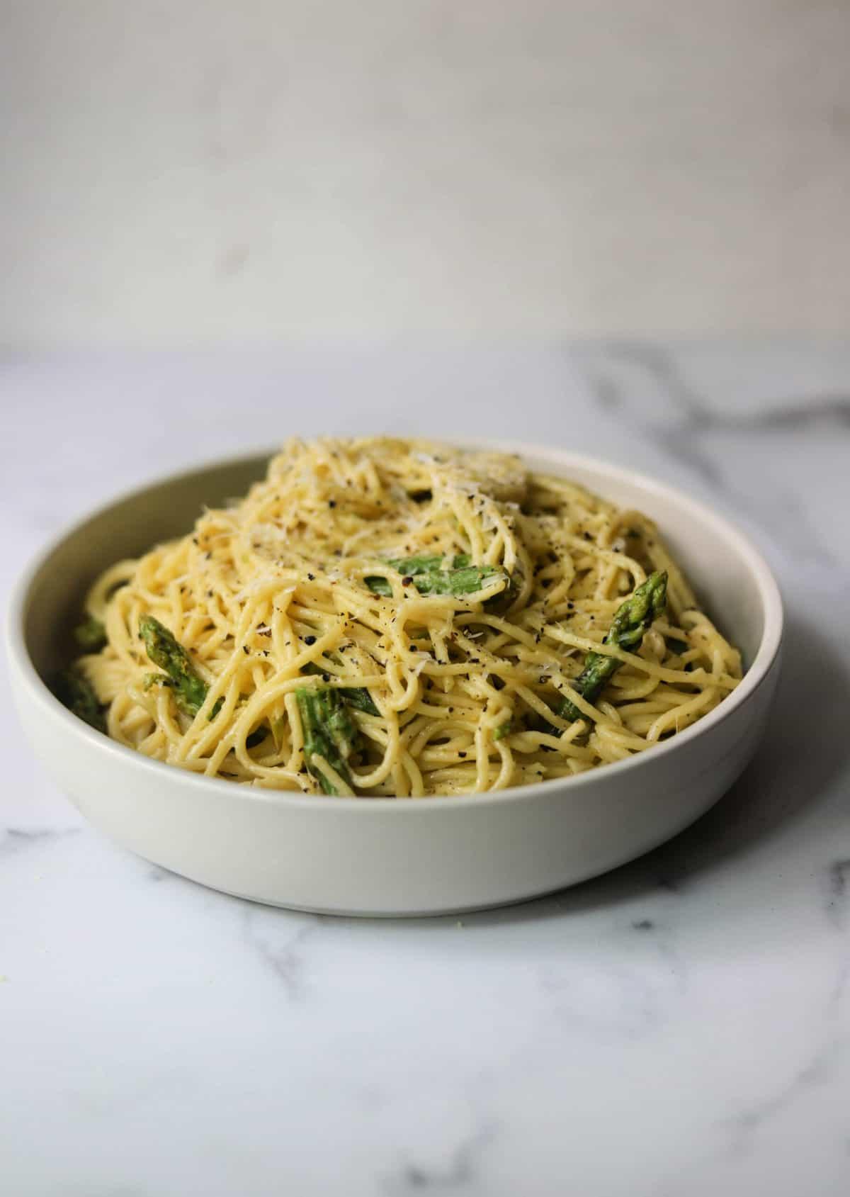 A white bowl with lemon asparagus pasta.