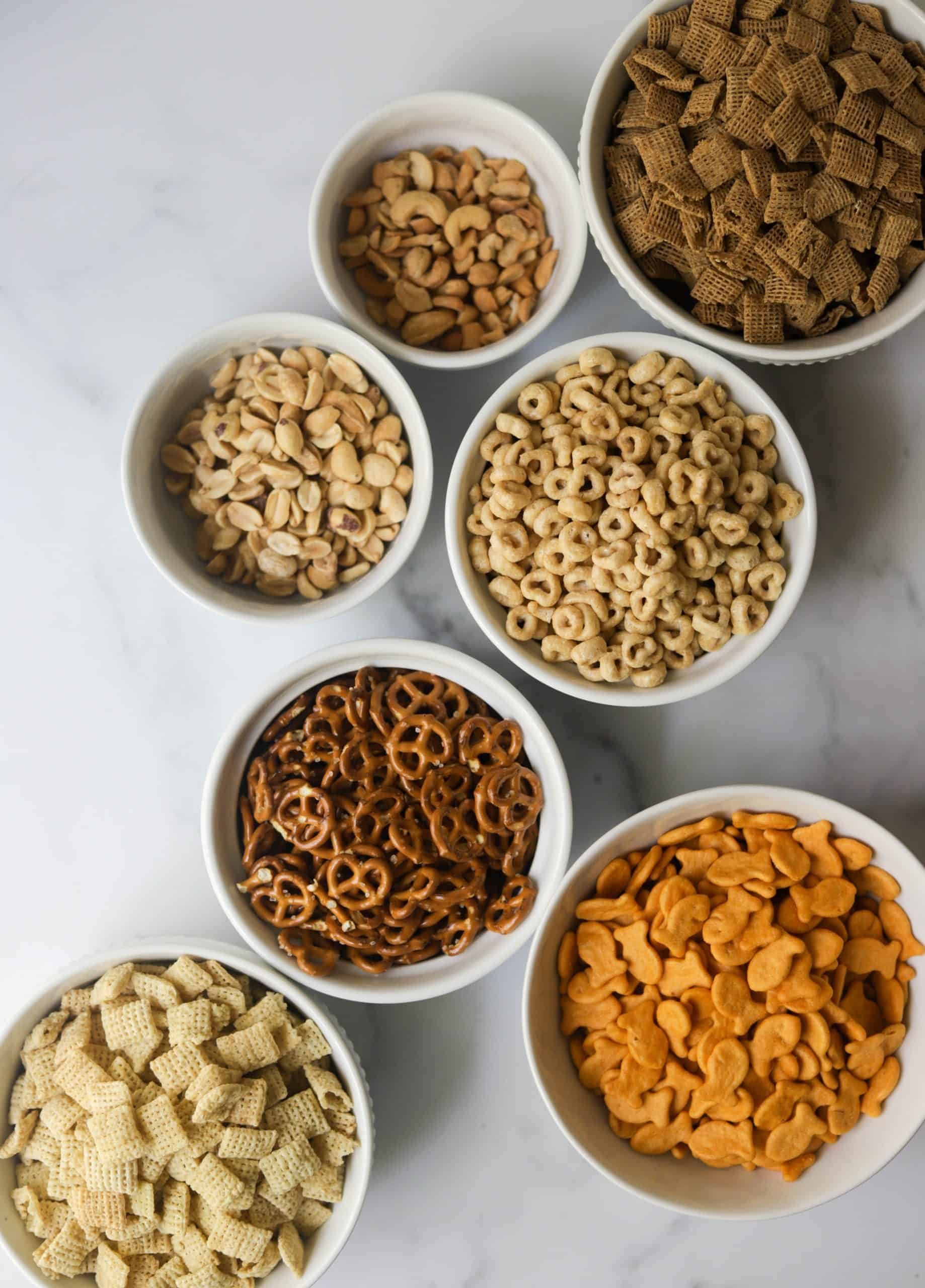 White bowls filled with chex mix ingredients.