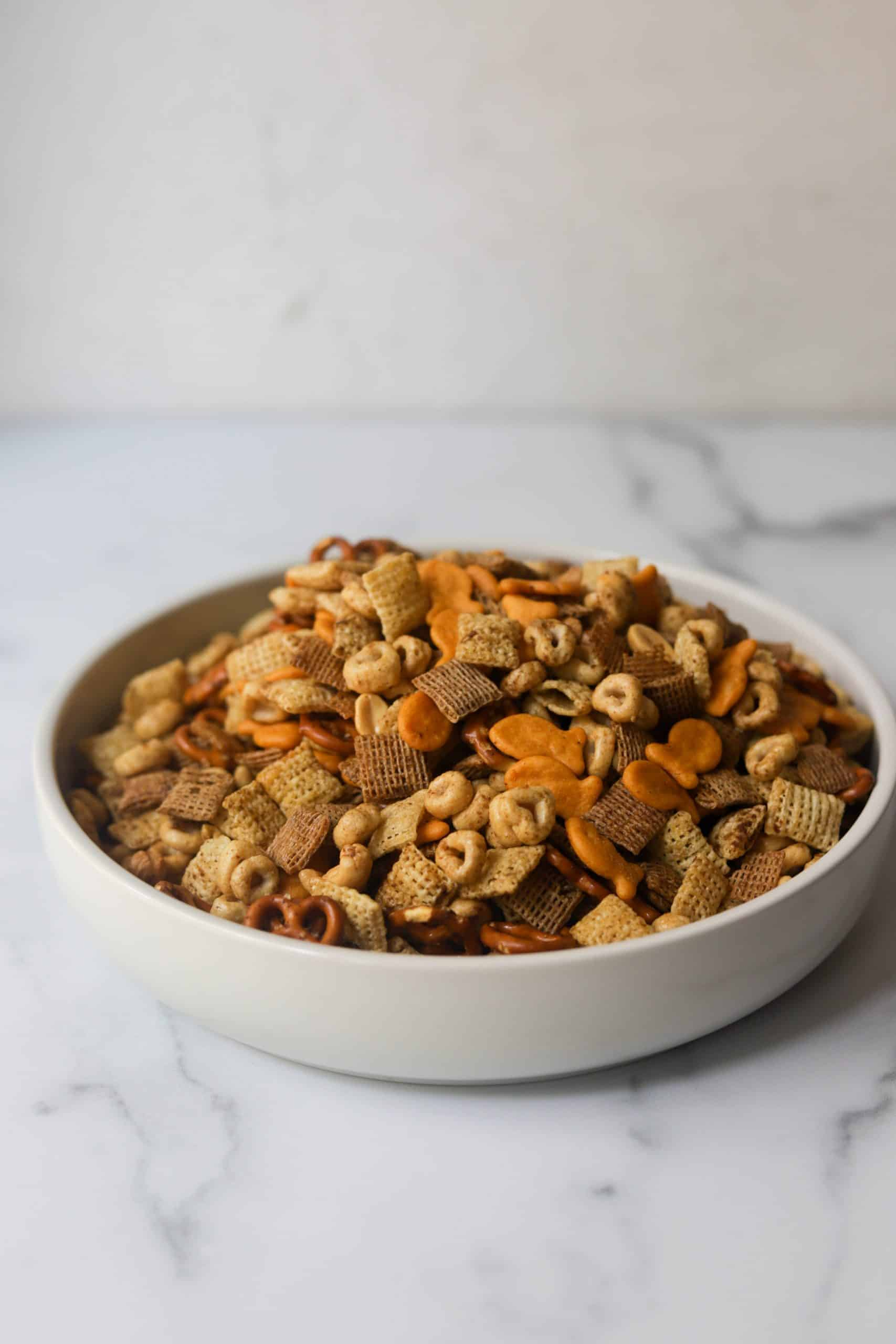 A side shot of a white bowl filled with chex mix.