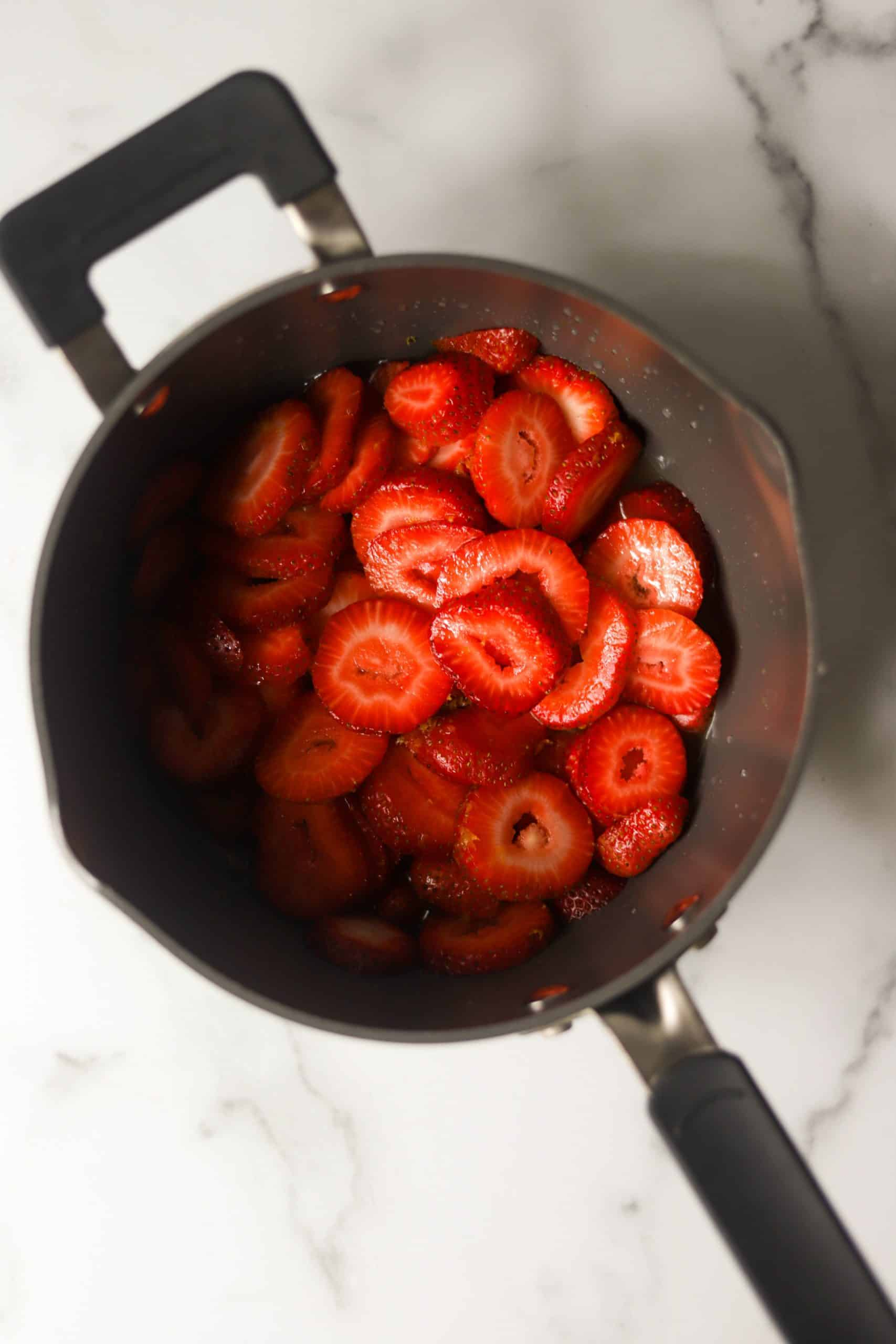 A saucepan filled with strawberries.