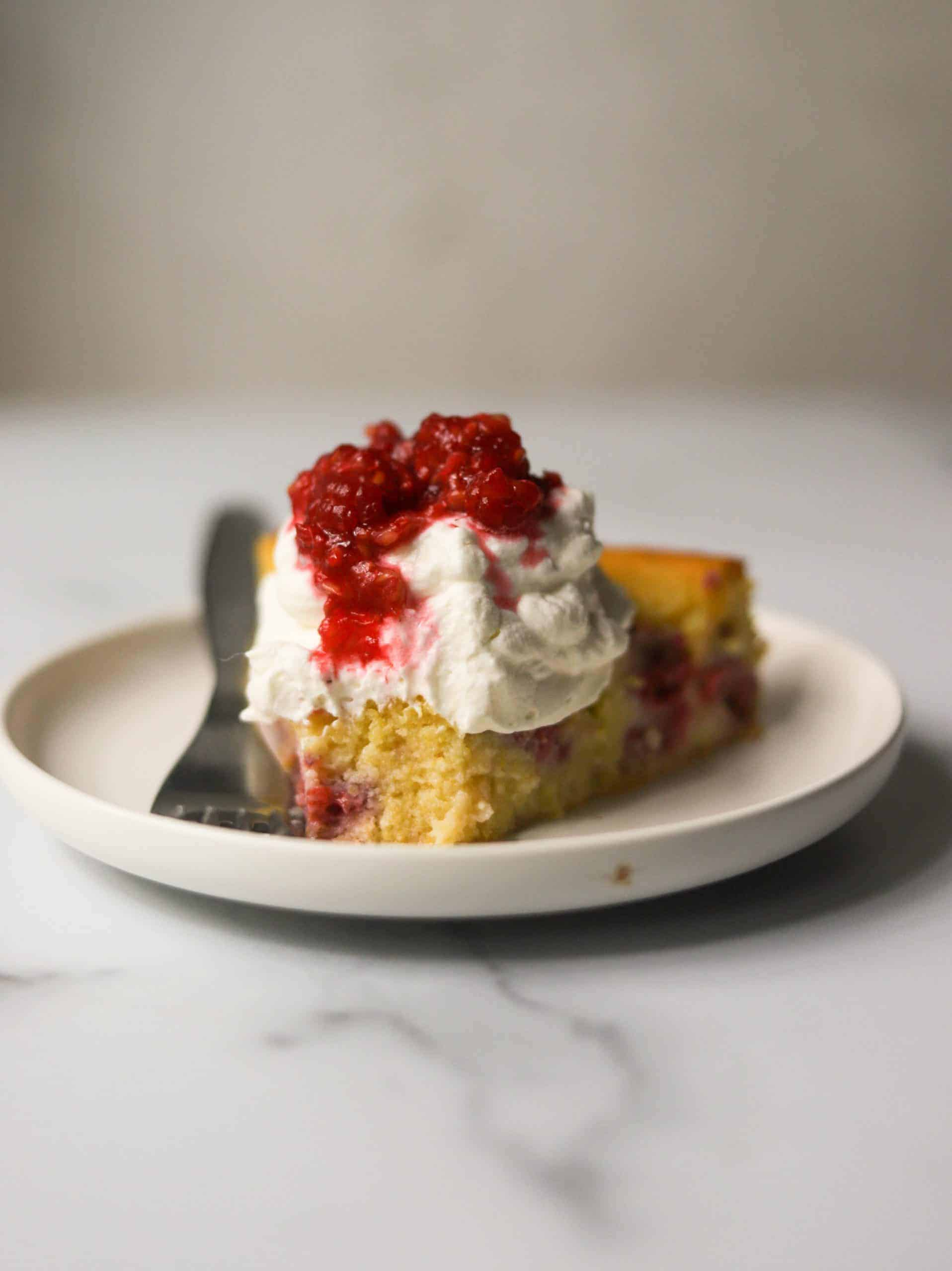 A slice of raspberry cake on a white plate with a bite missing.