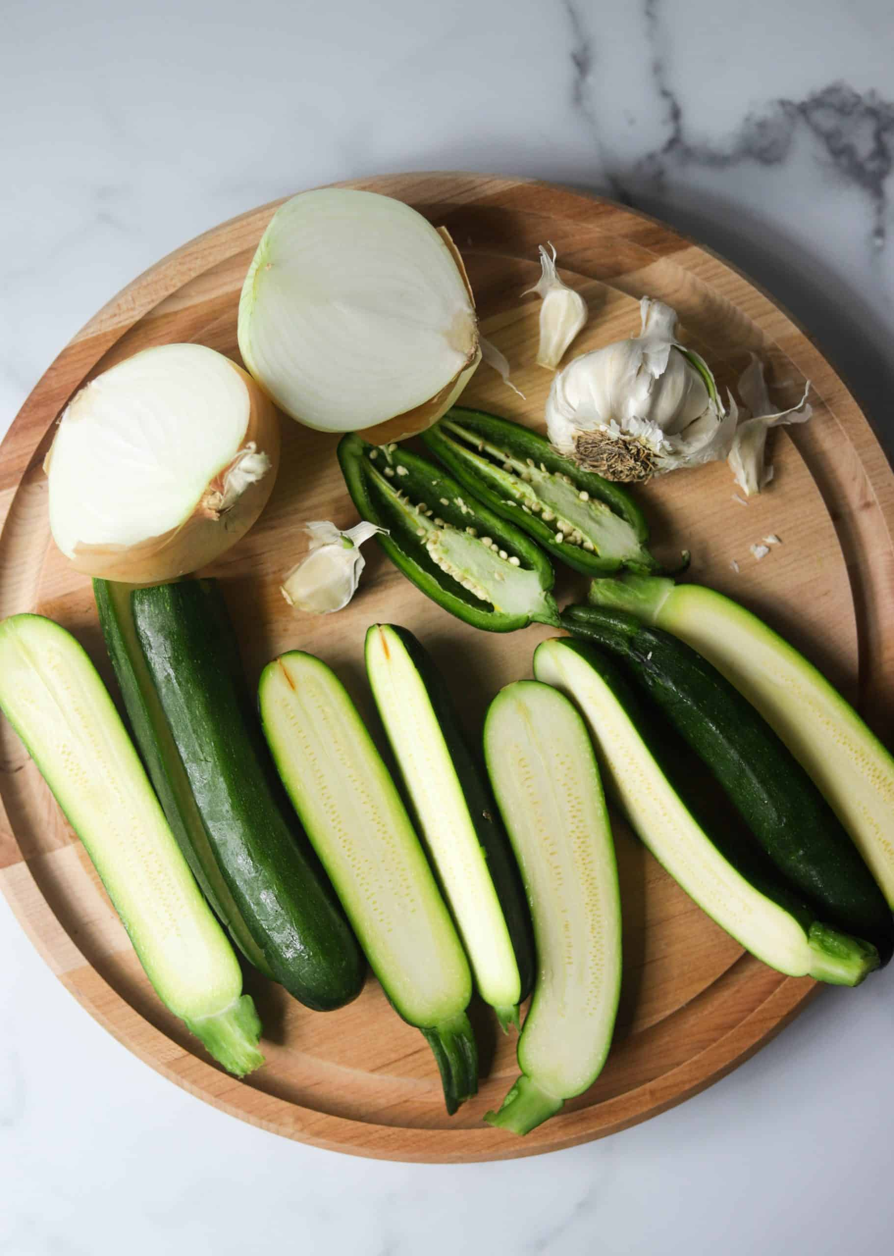 A wooden cutting board with zucchini soup ingredients.