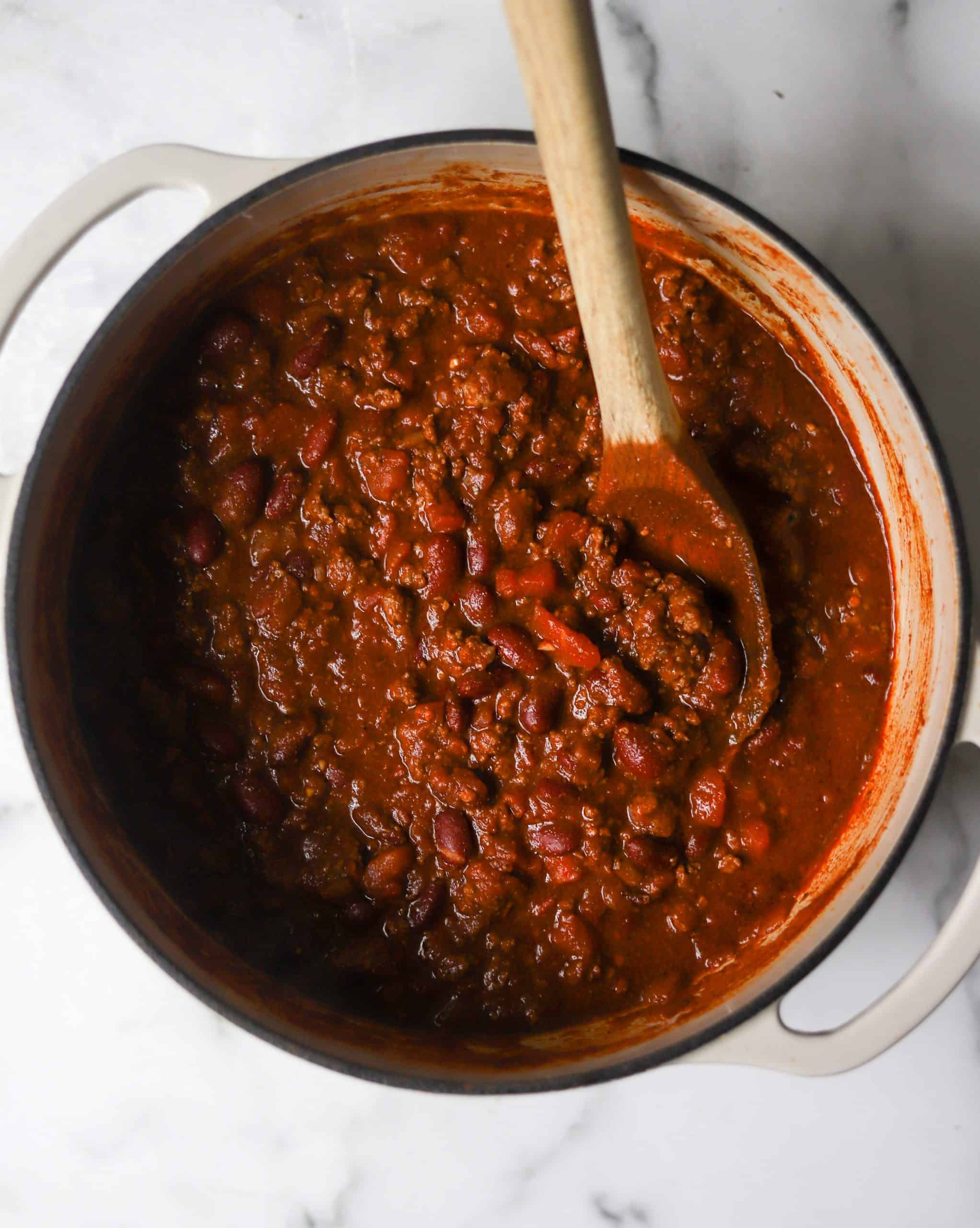 A white dutch oven filled with chili.
