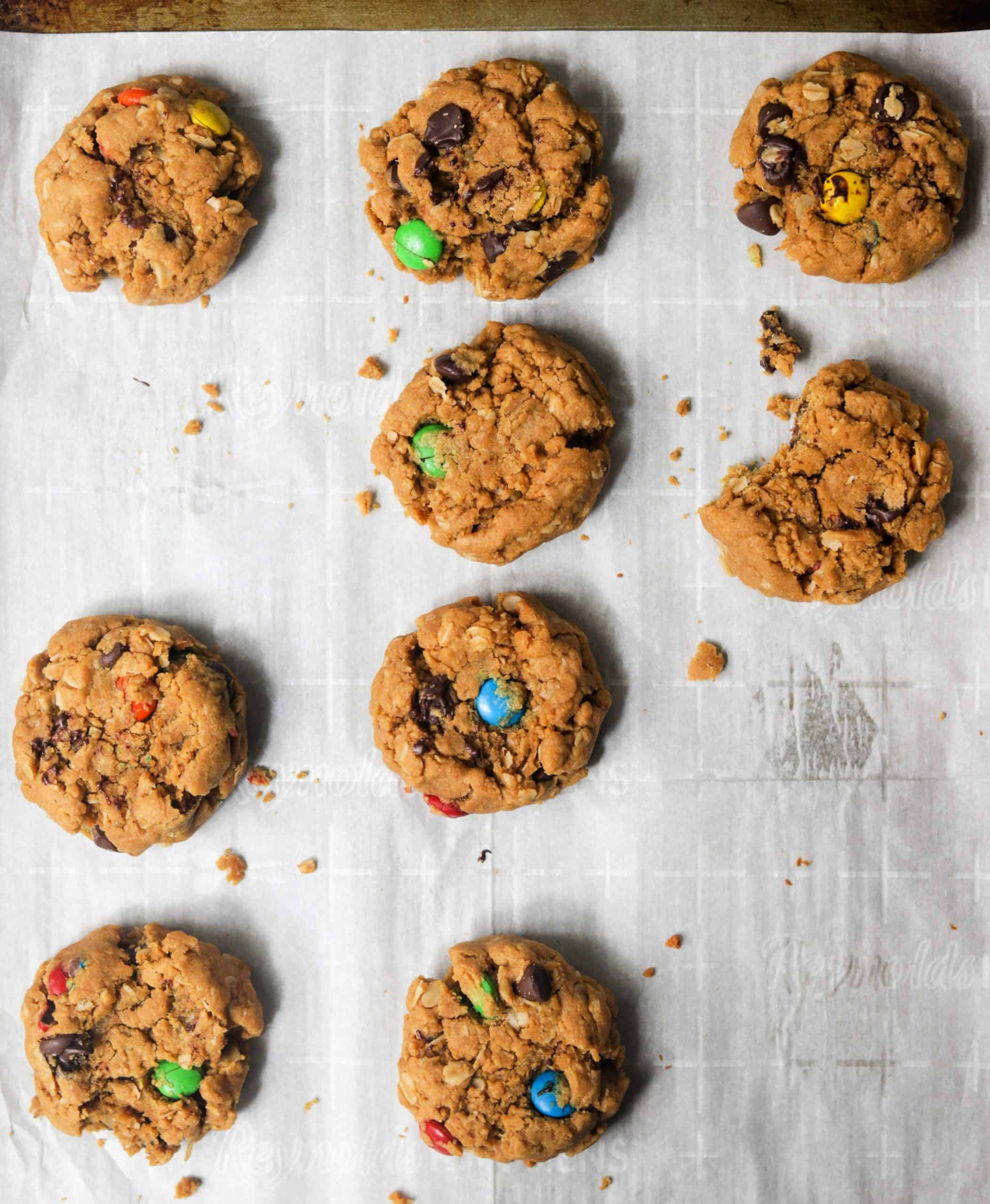 Monster cookies lined up on parchment paper.